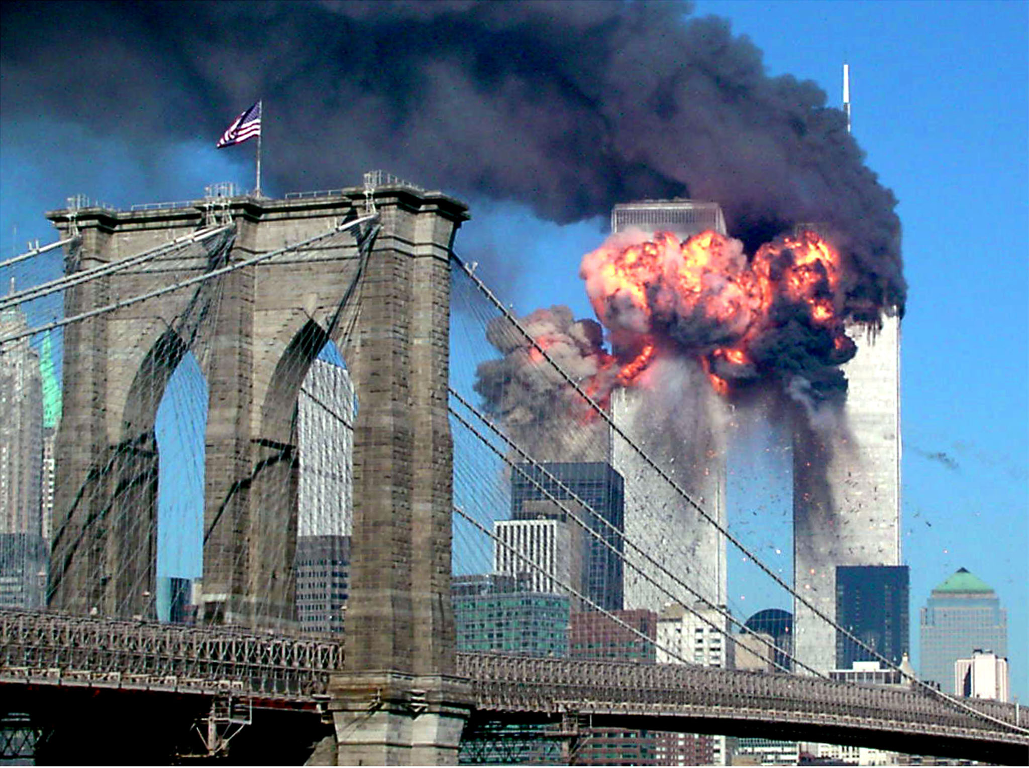 The second tower of the World Trade Center explodes into flames after being hit by a airplane, New York September 11, 2001 with the Brooklyn bridge in the foreground. Both towers of the complex collapsed after being hit by hijacked planes. REUTERS/Sara K. Schwittek