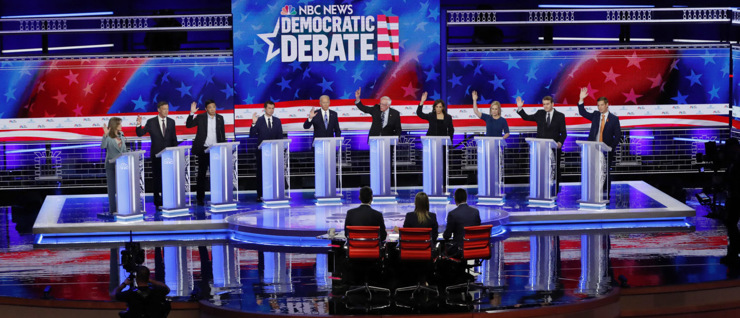 All ten Democratic presidential candidates raise their hands to indicate that they would provide Medicaid benefits to illegal immigrants during the second night of the first Democratic presidential candidates debate in Miami, Florida, U.S. June 27, 2019. (REUTERS/Mike Segar)
