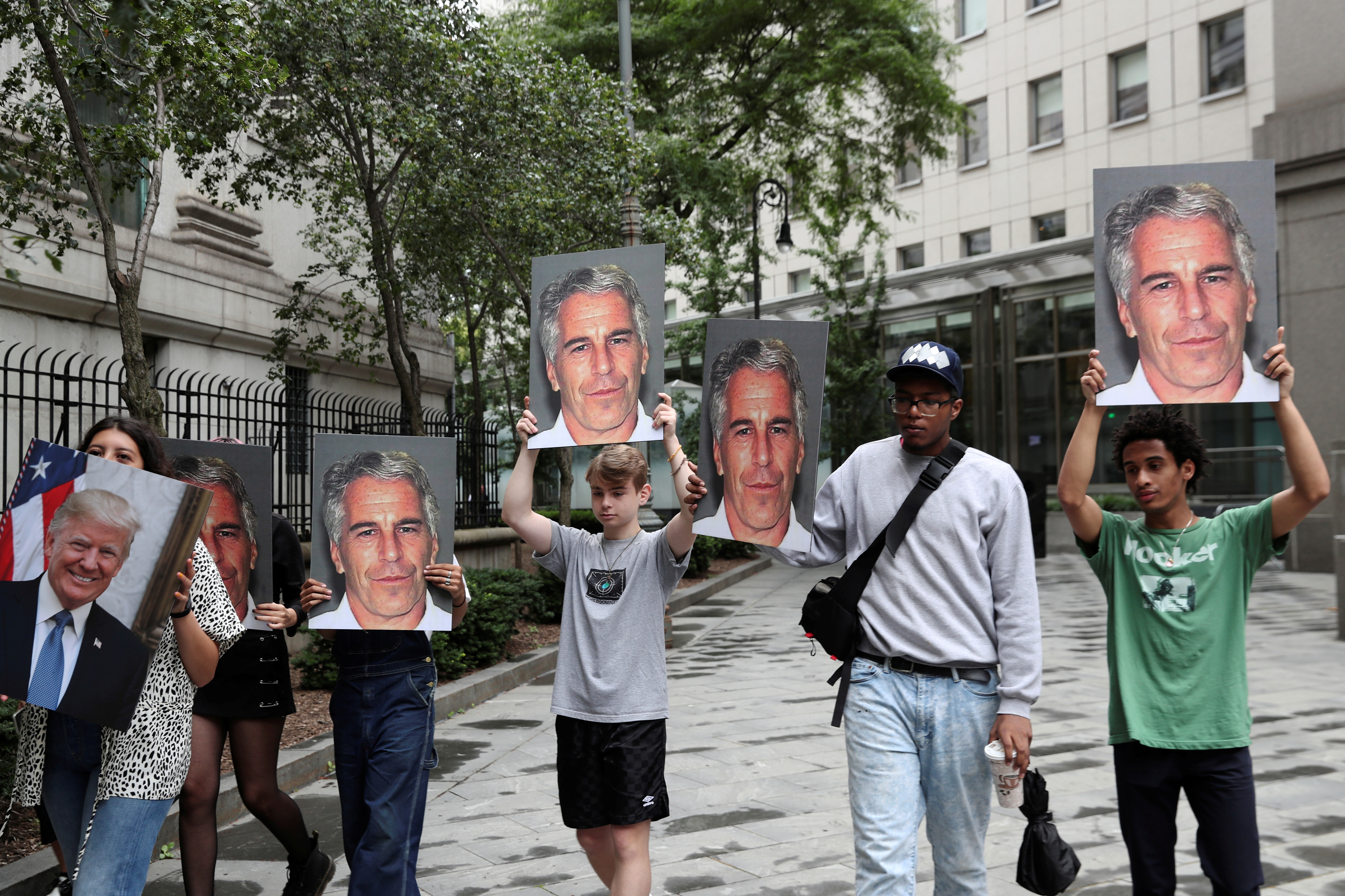 Demonstrators hold signs aloft protesting Jeffrey Epstein, as he awaits arraignment in the Southern District of New York on charges of sex trafficking of minors and conspiracy to commit sex trafficking of minors, in New York, U.S., July 8, 2019. REUTERS/Shannon Stapleton