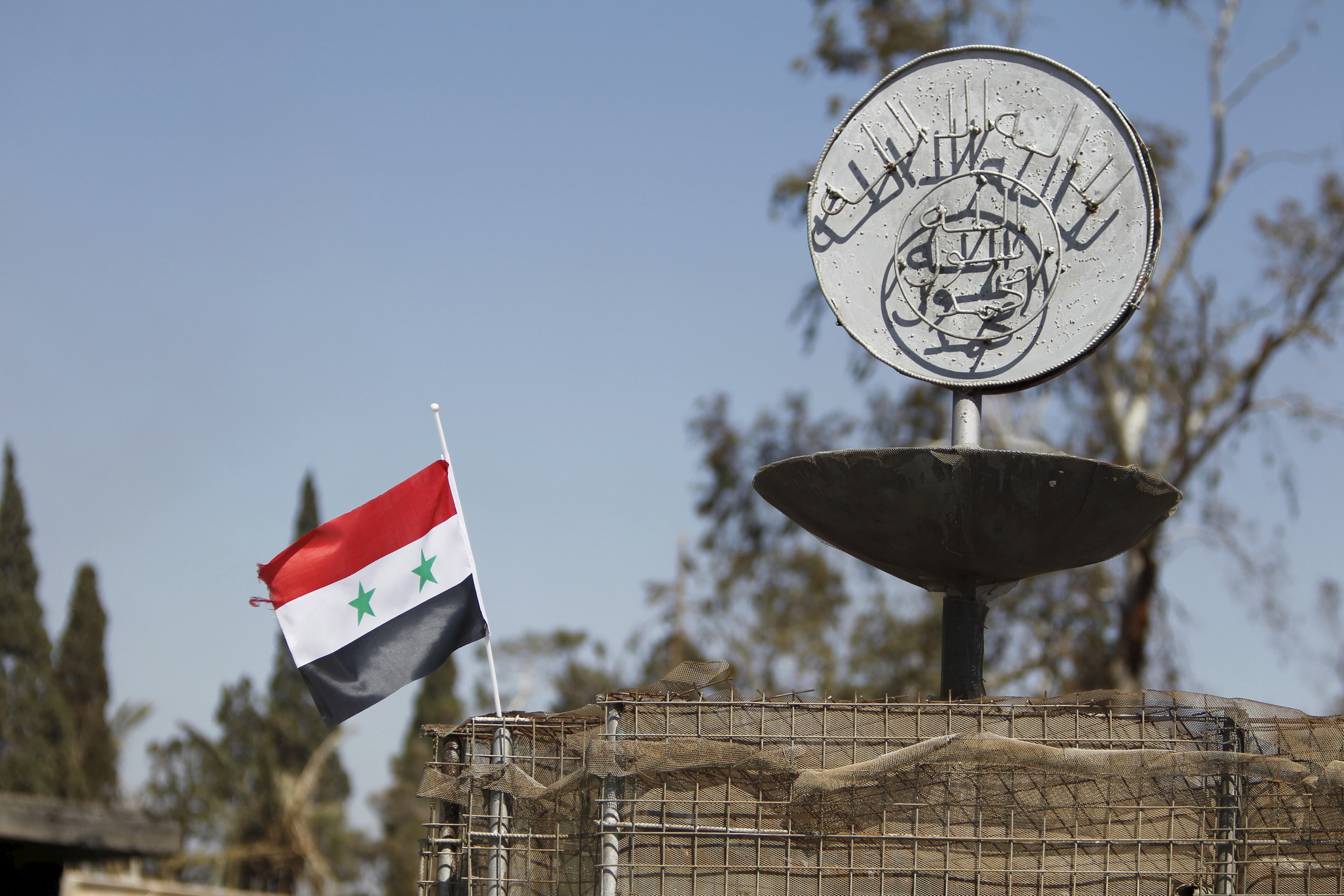 A Syrian national flag flutters next to the Islamic State's slogan at a roundabout where executions were carried out by ISIS militants in the city of Palmyra, in Homs Governorate, Syria April 1, 2016. REUTERS/Omar Sanadiki