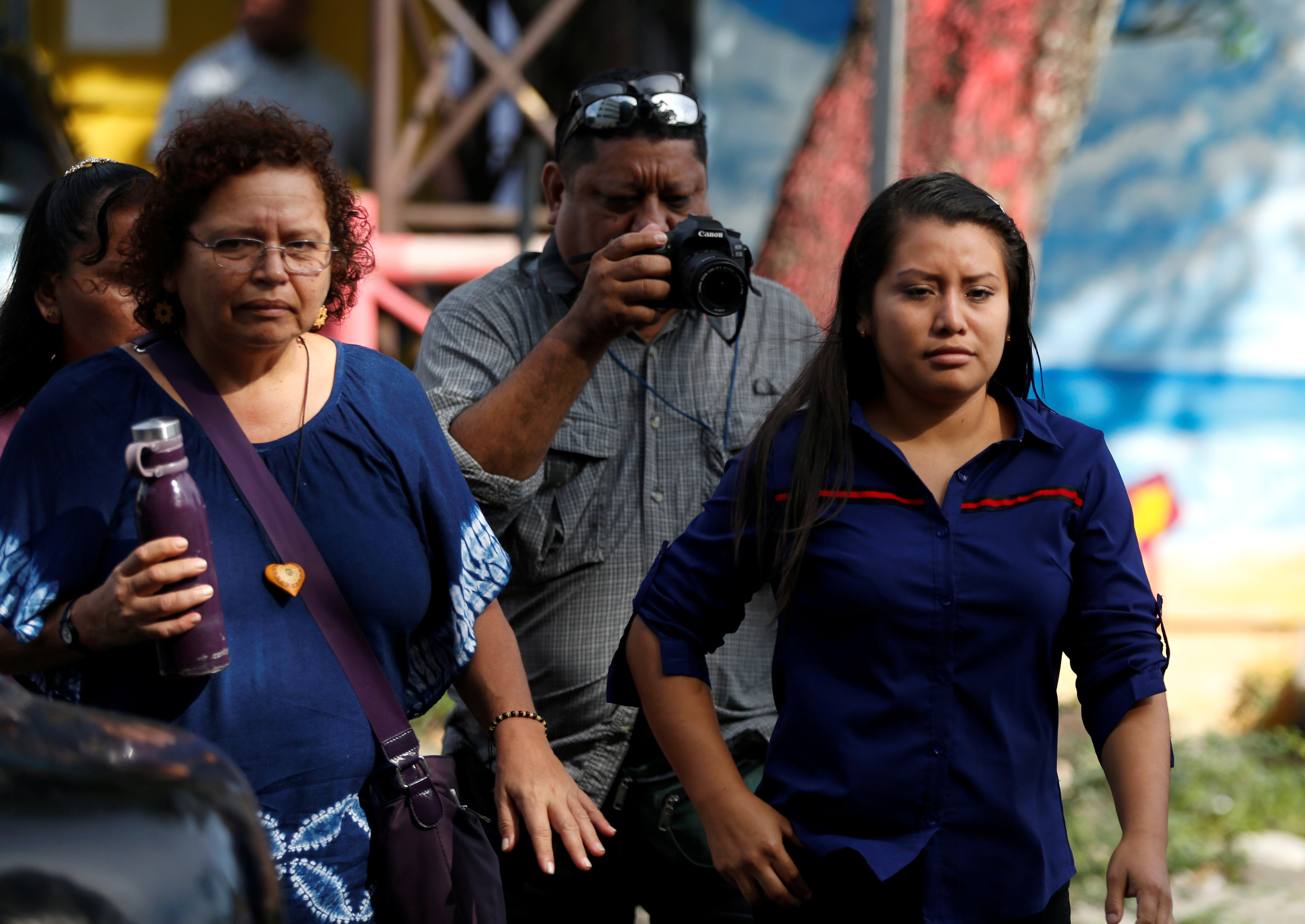"""Evelyn Hernandez, who was sentenced to 30 years in prison for a suspected abortion, arrives with Salvadoran feminist and social activist Morena Herrera for a hearing in Ciudad Delgado, El Salvador July 15, 2019. Placards read """"Justice for Evelyn"""". REUTERS/Jose Cabezas - RC1BD2C1A0E0"""