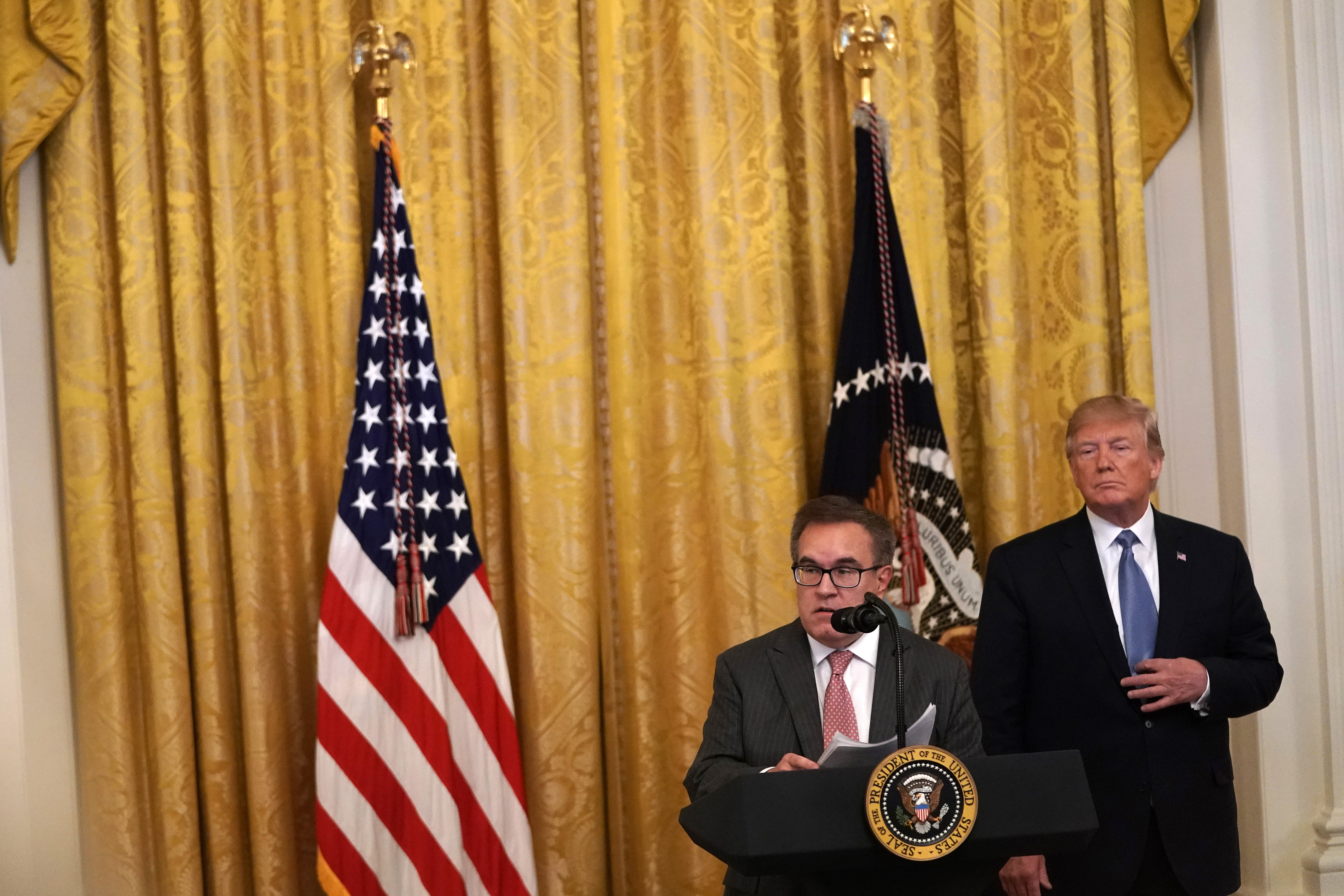 """WASHINGTON, DC - JULY 08: U.S. Environmental Protection Agency Administrator Andrew Wheeler (L) speaks as President Donald Trump (R) looks on during an East Room event on the environment July 7, 2019 at the White House in Washington, DC. President Trump delivered remarks on """"his Administration's environmental accomplishments of cleaner air and cleaner water, including helping communities across the Nation reduce air pollution and meet our air quality standards, as well as modernize outdated infrastructure and improve water quality while at the same time growing a strong economy for all Americans."""" (Photo by Alex Wong/Getty Images)"""