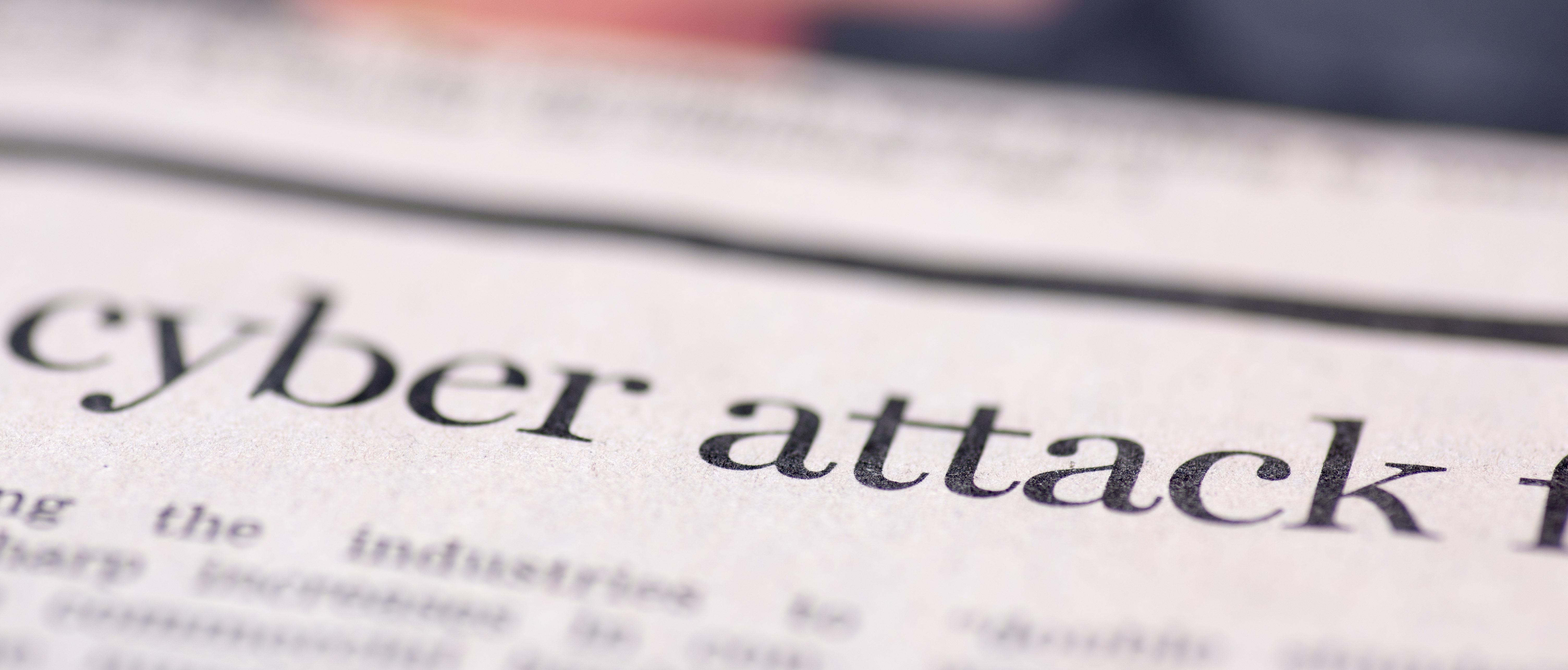 "A newspaper has ""cyber attack"" in a headline. Shutterstock image via arda savasciogullari"