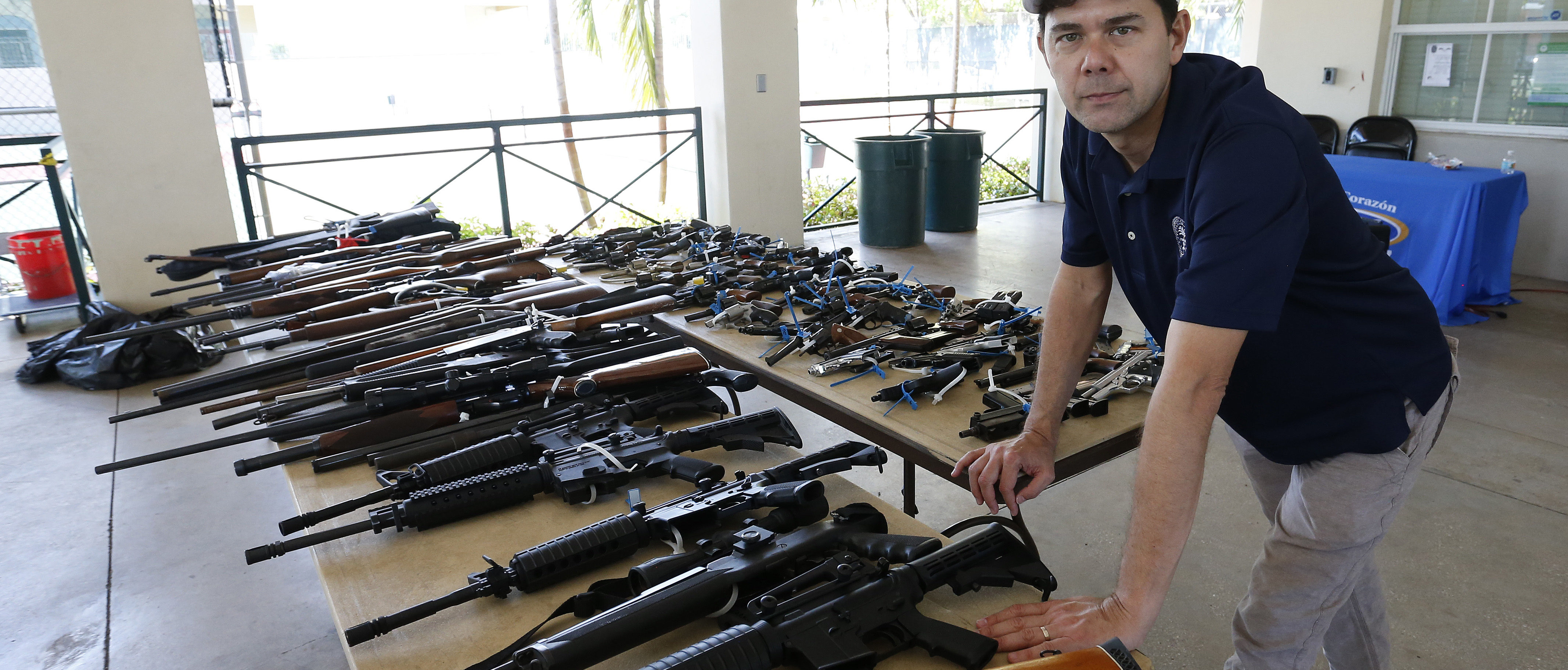 City of Miami Commissioner Ken Russell poses in front of the guns surrendered during a City of Miami gun buyback event in Miami, Florida on March 17, 2018. (Photo by RHONA WISE/AFP/Getty Images)