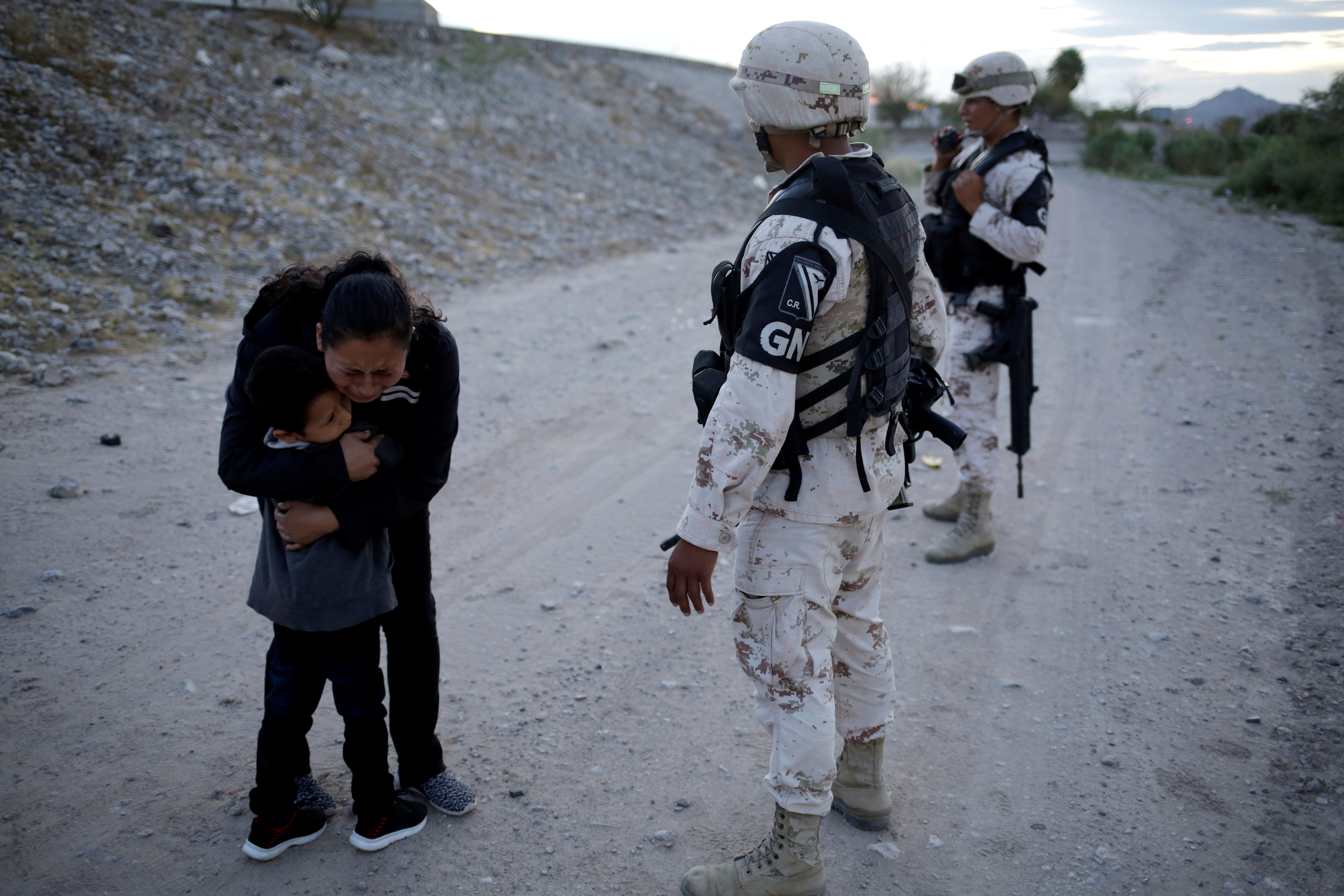 Guatemalan migrant Ledy Perez embraces her son Anthony while asking to members of the Mexican National Guard to let them cross into the United States, as seen from Ciudad Juarez, Mexico July 22, 2019. REUTERS/Jose Luis Gonzalez