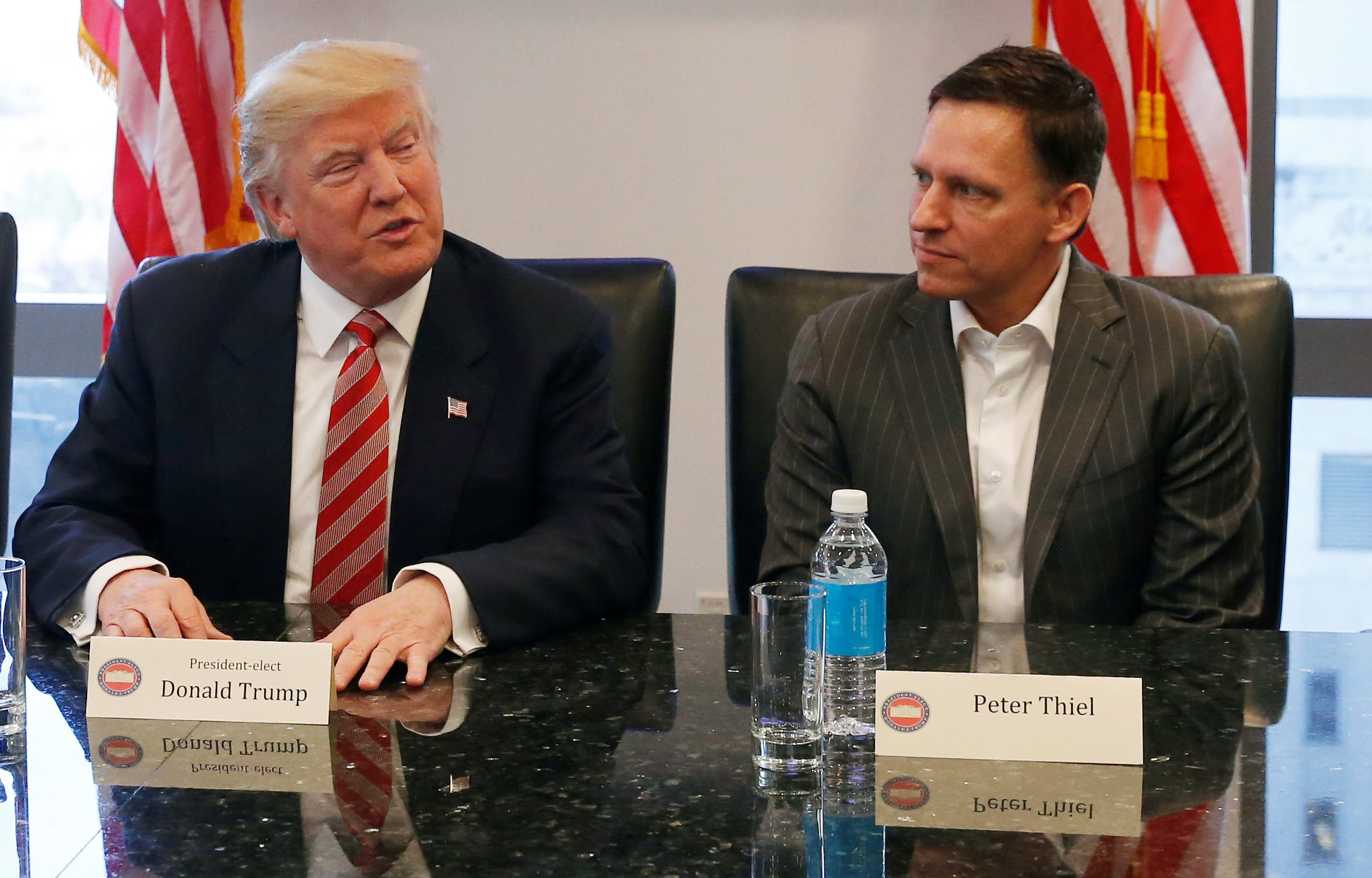 U.S. President-elect Donald Trump speaks while PayPal co-founder and Facebook board member Peter Thiel and Apple Inc CEO Tim Cook look on during a meeting with technology leaders at Trump Tower in New York U.S., December 14, 2016. REUTERS/Shannon Stapleton - RC1838328880