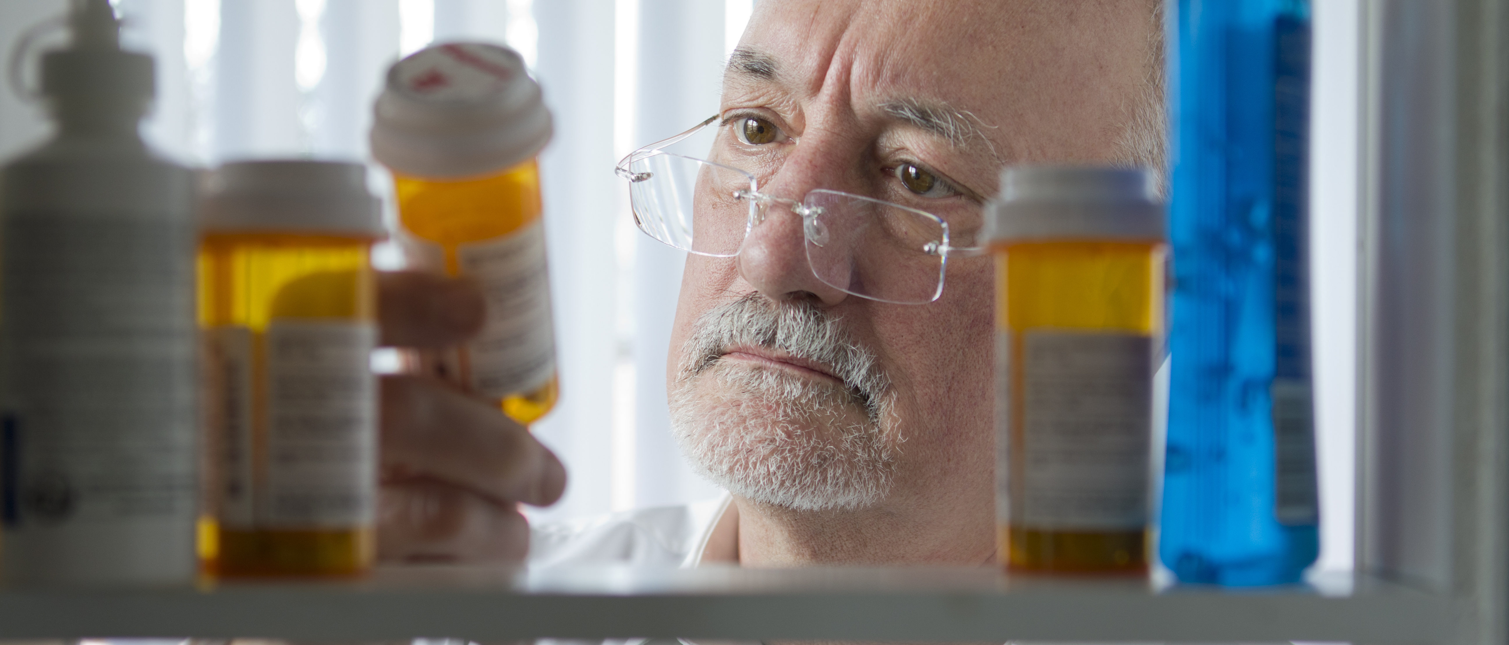 A man looks at a bottle of prescription drugs. Shutterstock photo via Burlingham