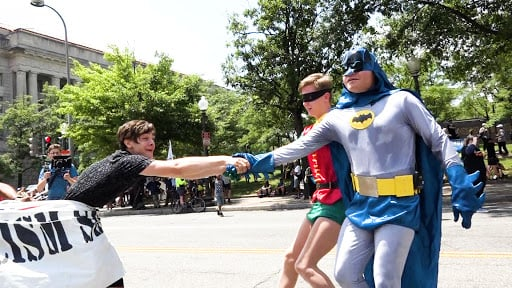 Batman and Robin rescuing a boy from a banner Antifa was using to pull him away.