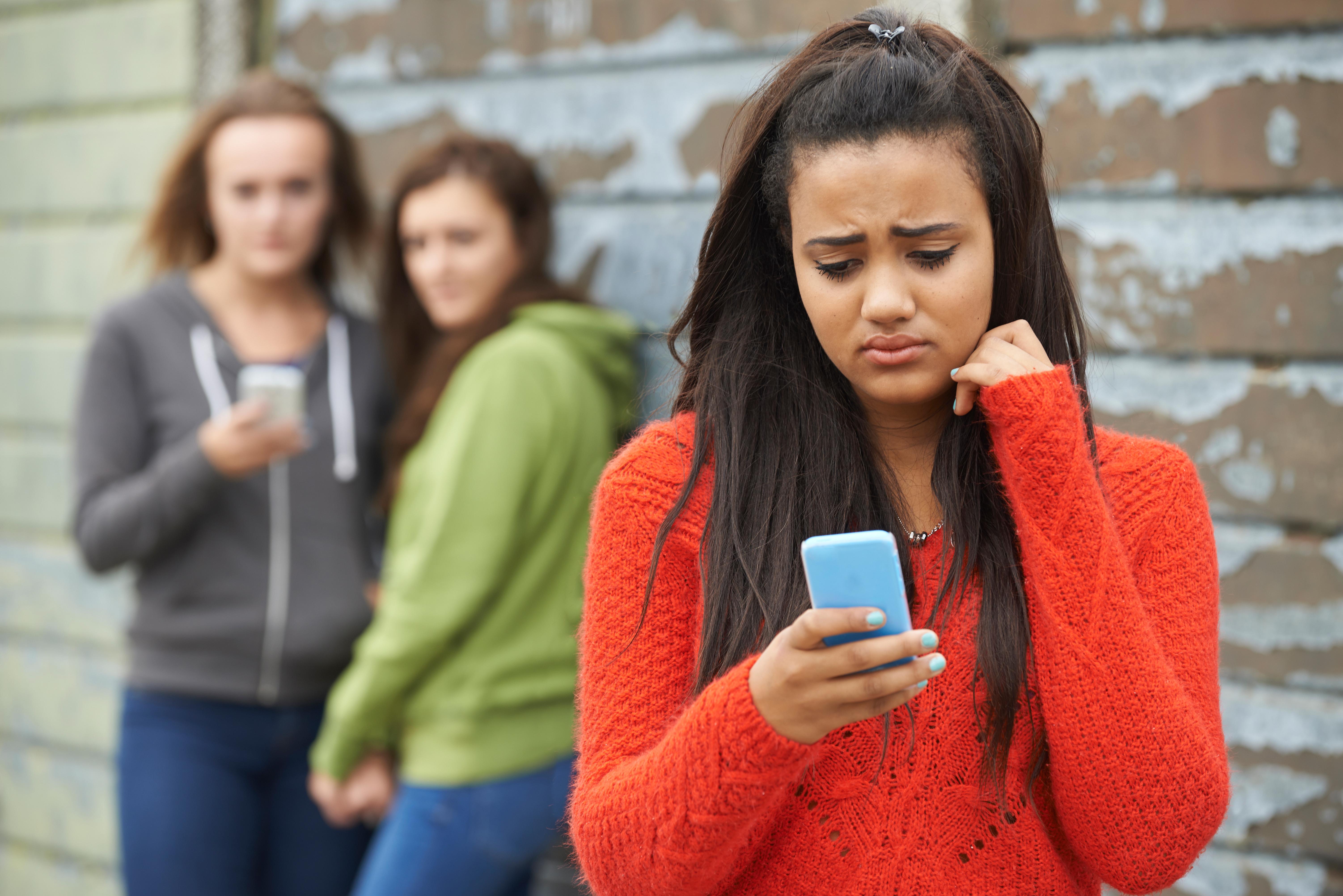 Teenage Girl Being Bullied By Text Message. SpeedKingz/Shutterstock