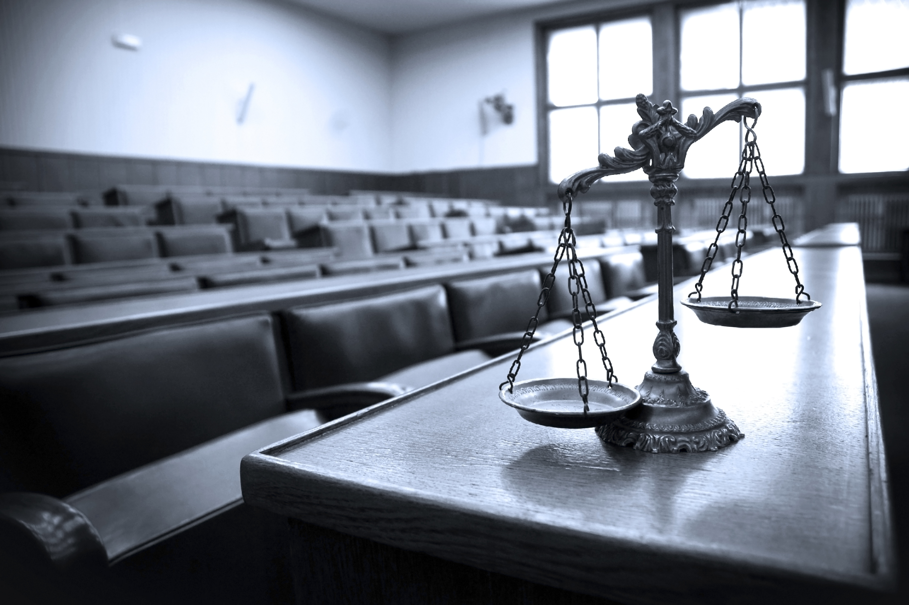 A courtroom is depicted in black-and-white. Shutterstock image via tlegend