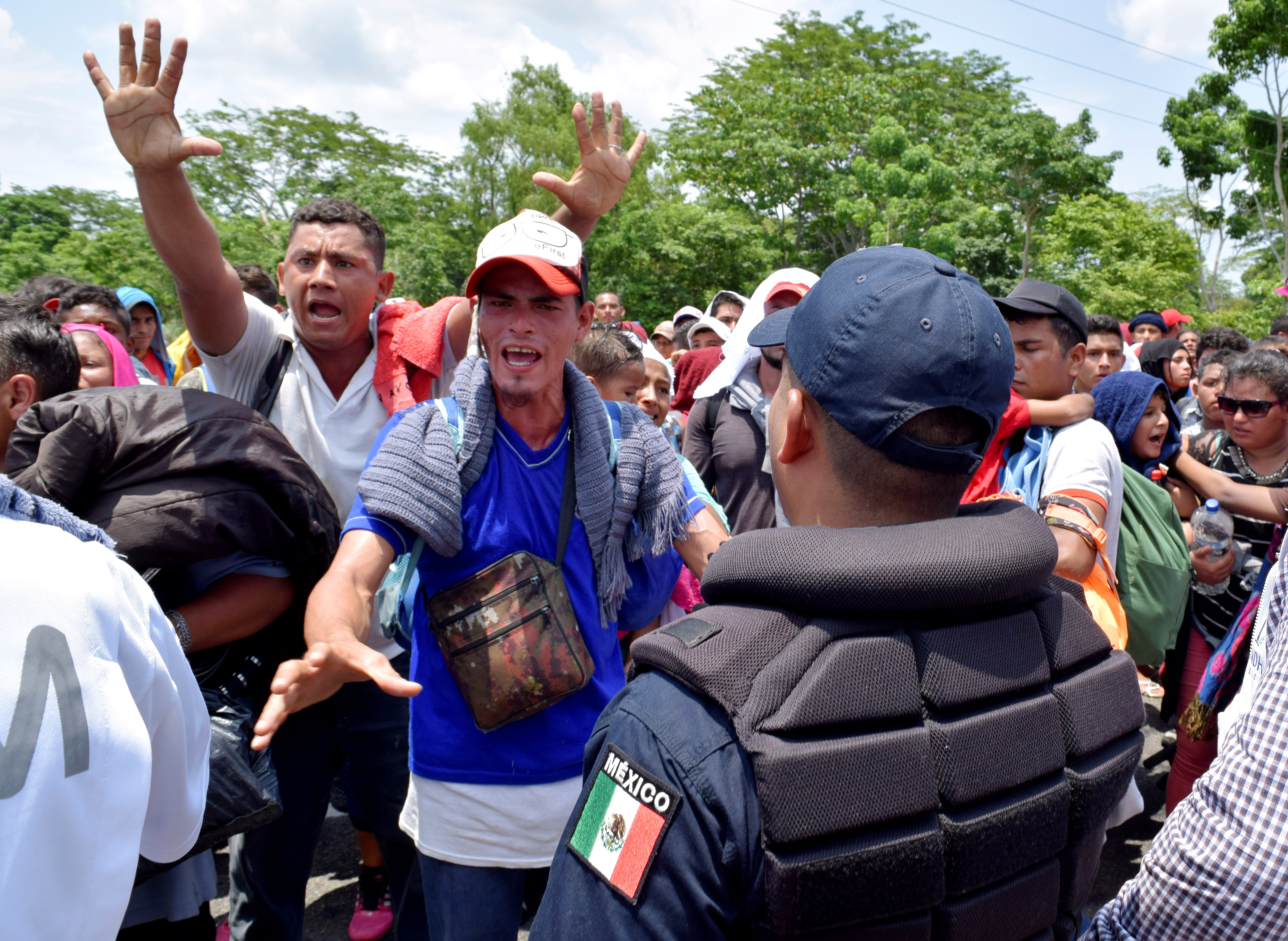 Migrants gesture while arguing with a federal police officer during a joint operation by the Mexican government to stop a caravan of Central American migrants on their way to the U.S., at Metapa de Dominguez