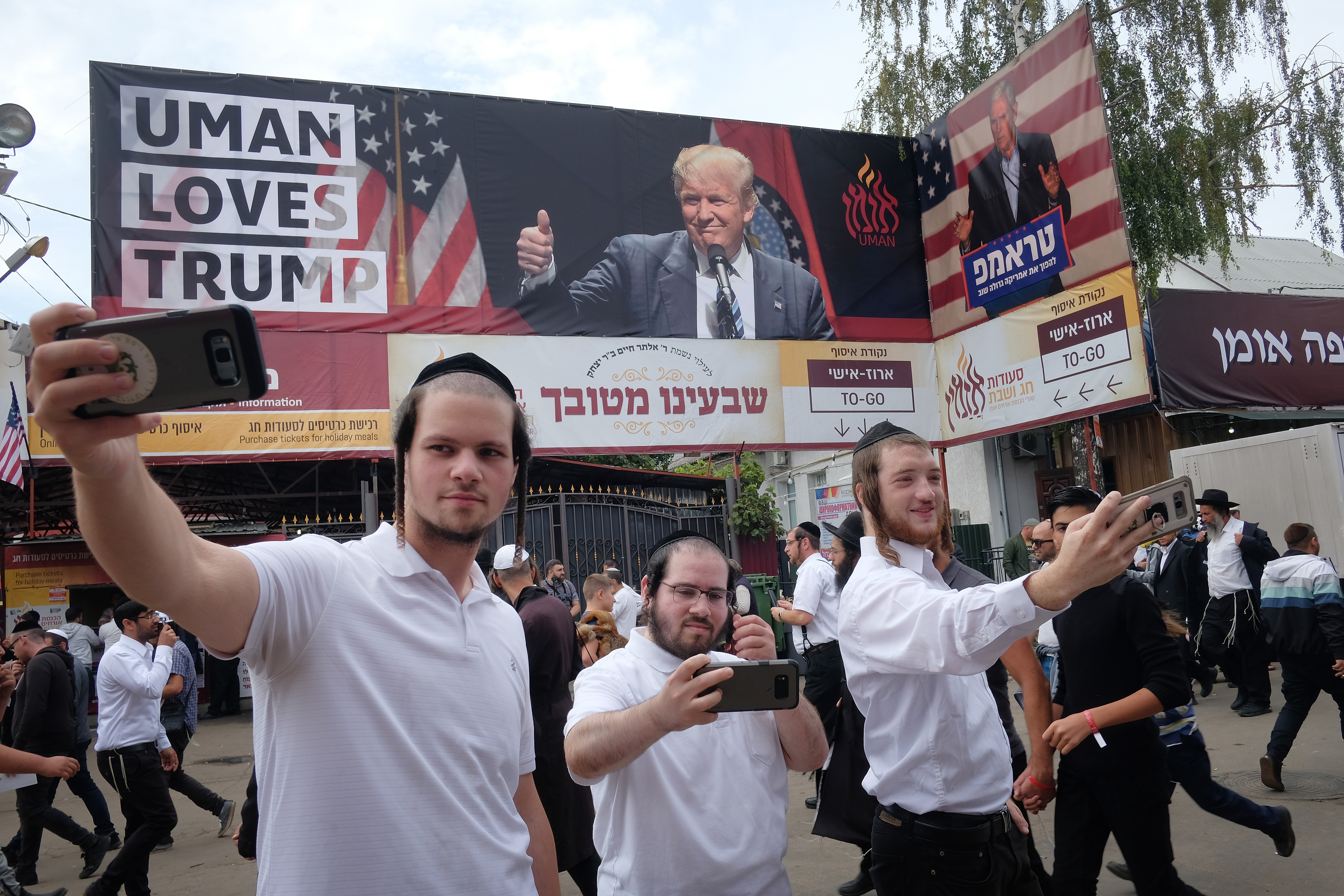 "Hassidic Jews shoot selfies under a banner that reads: ""Uman Loves Trump"", in reference to U.S. President Donald Trump, who is popular among Orthodox Jews, prior to the annual Rosh Hashanah celebration on September 9, 2018 in Uman, Ukraine. (Photo by Sean Gallup/Getty Images)"