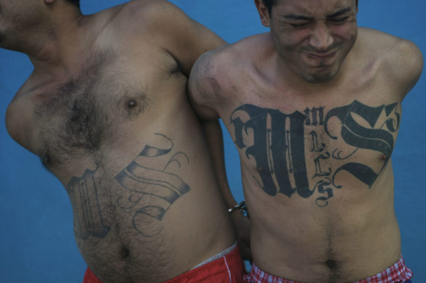 Two members of the Mara Salvatrucha gang are pictured after being detained by Salvadoran army soldiers and policemen during an operation in San Salvador, on January 19, 2019. (Photo by MARVIN RECINOS / AFP / Getty)