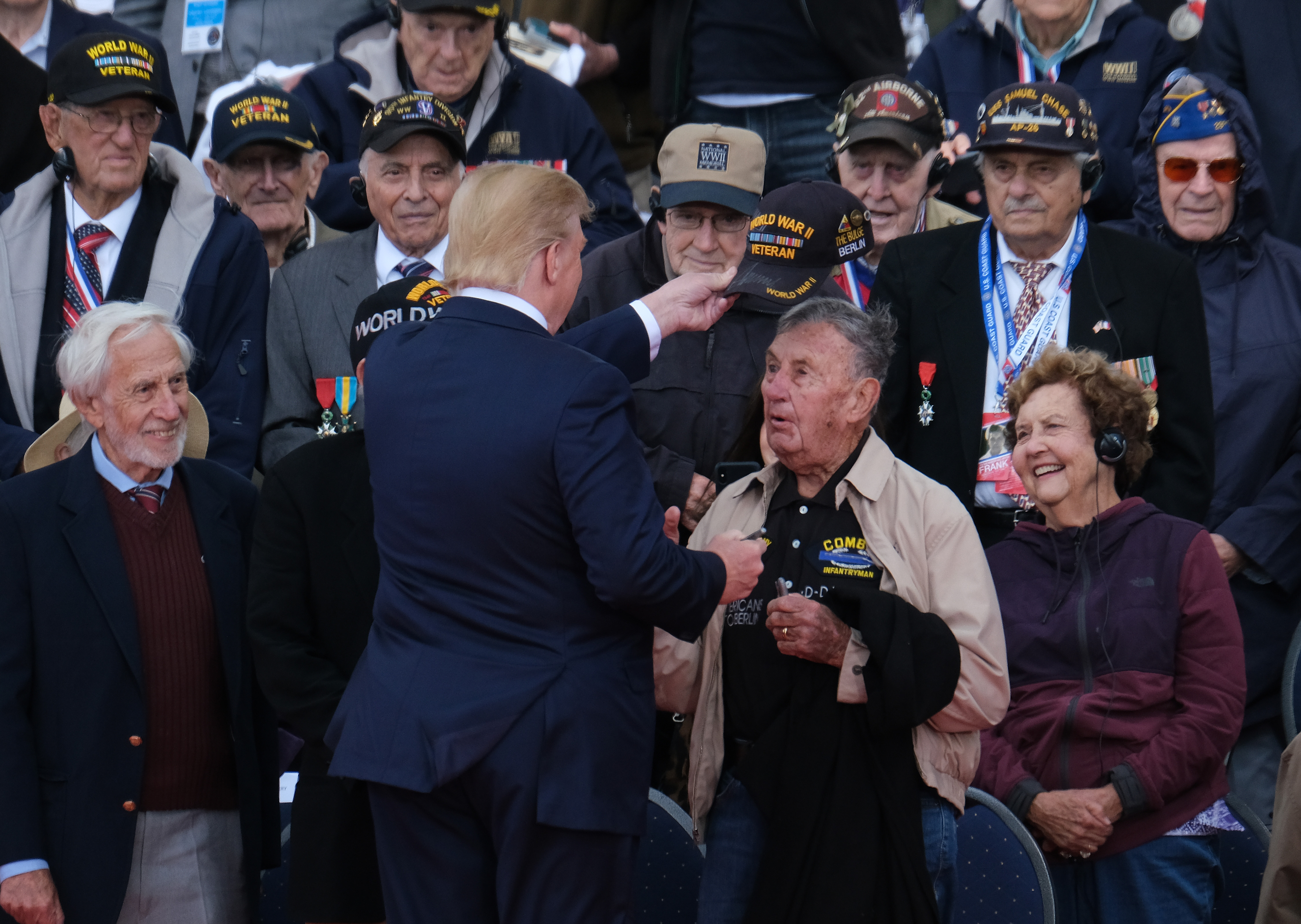 U.S. President Donald Trump tips the cap of a U.S. veteran of the Battle of Normandy as other veterans look on during the main ceremony to mark the 75th anniversary of the World War II Allied D-Day invasion of Normandy at Normandy American Cemetery on June 06, 2019. (Sean Gallup/Getty Images)
