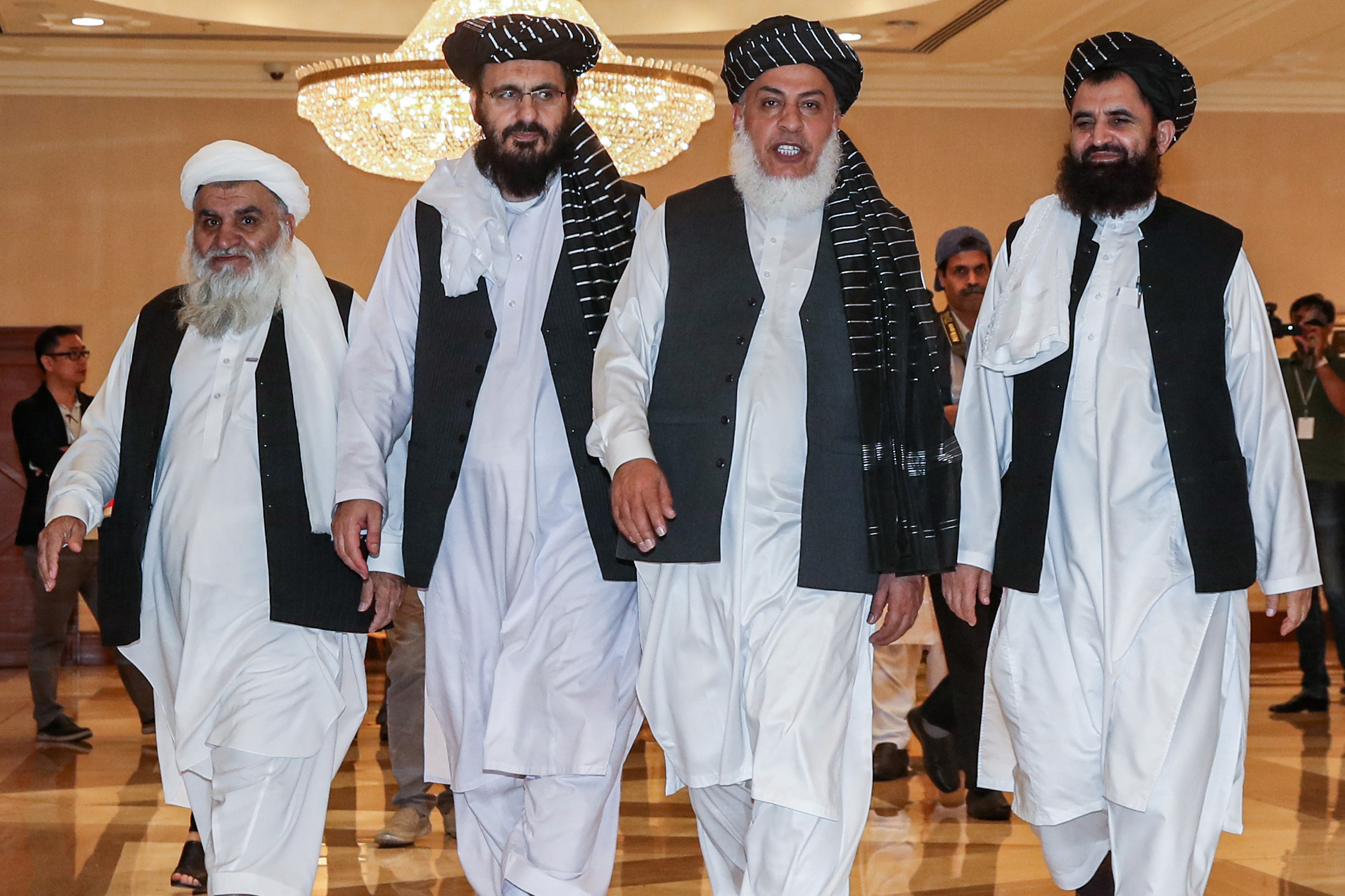 Mohammad Nabi Omari (C-L), a Taliban member formerly held by the US at Guantanamo Bay and reportedly released in 2014 in a prisoner exchange, Taliban negotiator Abbas Stanikzai (C-R), and former Taliban intelligence deputy Mawlawi Abdul Haq Wasiq (R) walk with another Taliban member during the second day of the Intra Afghan Dialogue talks in the Qatari capital Doha on July 8, 2019. (KARIM JAAFAR/AFP/Getty Images)