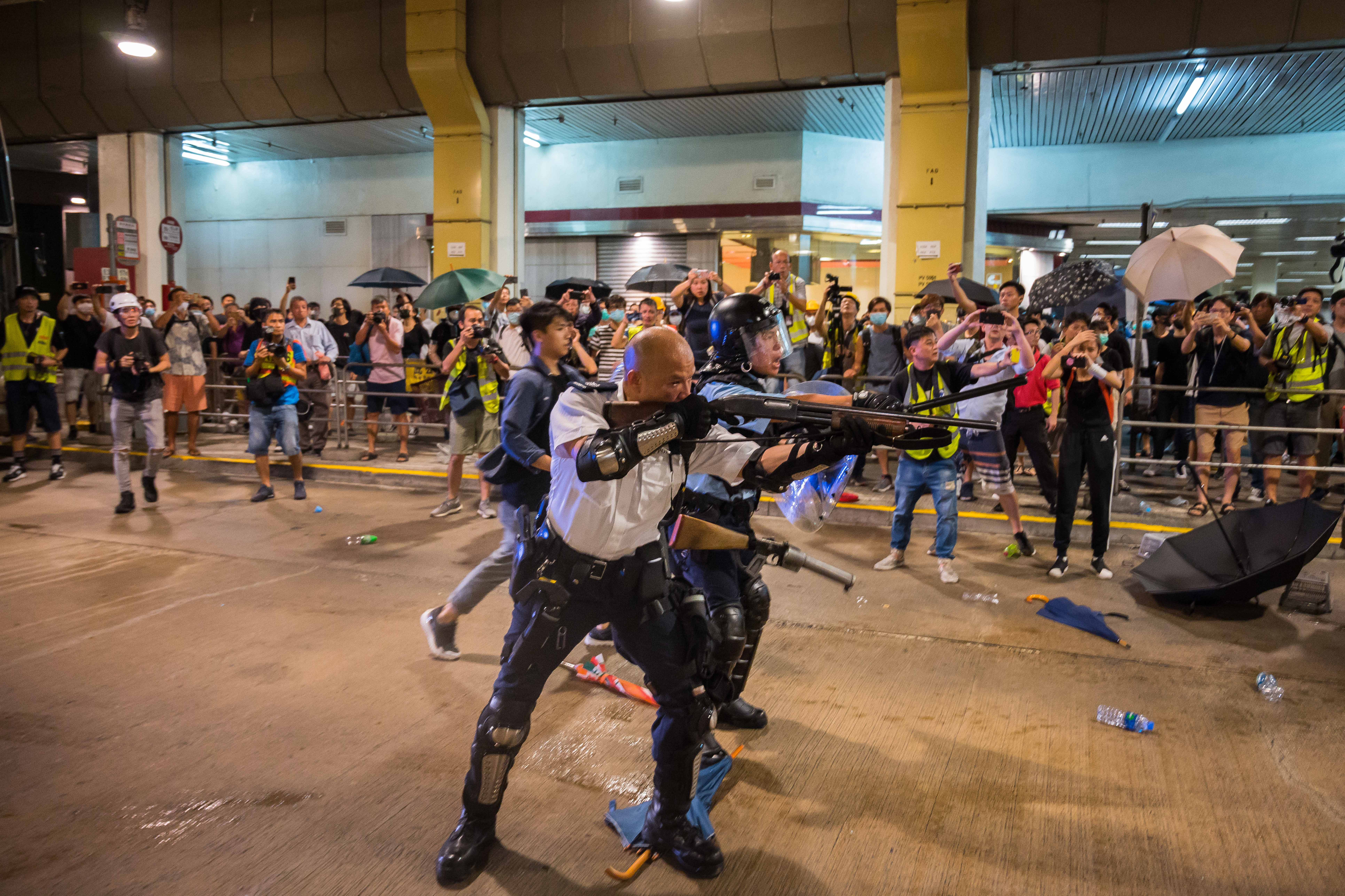 A riot police officer holds a shotgun towards protestors during a demonstration on July 30, 2019 in Hong Kong, China. Protesters have continued weekly rallies on the streets of Hong Kong (Photo by Billy H.C. Kwok/Getty Images)