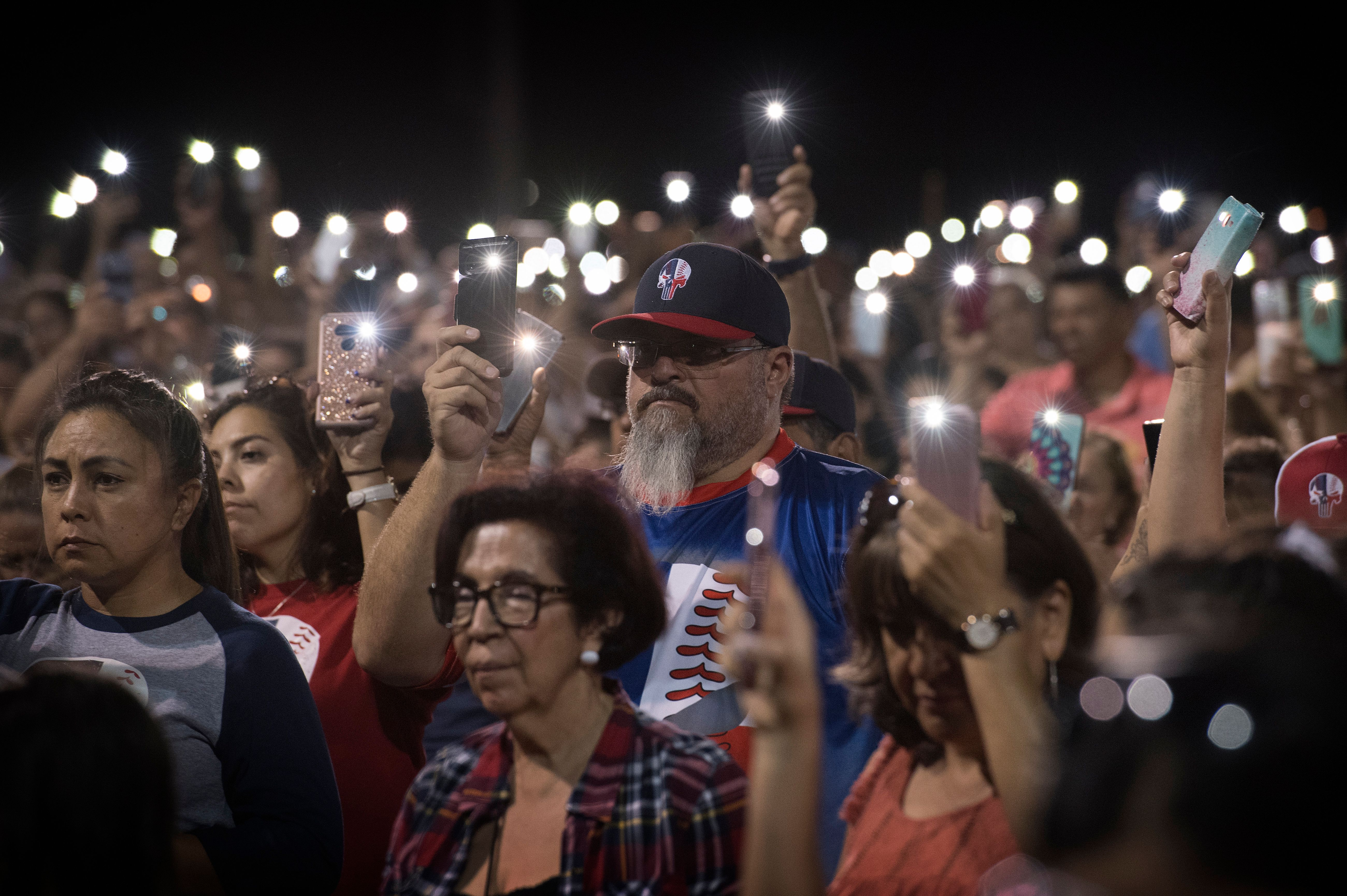 People hold up their phones during a prayer and candle vigil organized by the city, after a shooting left 20 people dead at the Cielo Vista Mall Wal-Mart in El Paso, Texas, on August 4, 2019. - The United States mourned Sunday for victims of two mass shootings that killed 29 people in less than 24 hours as debate raged over whether President Donald Trump's rhetoric was partly to blame for surging gun violence. The rampages turned innocent snippets of everyday life into nightmares of bloodshed: 20 people were shot dead while shopping at a crowded Walmart in El Paso, Texas on Saturday morning, and nine more outside a bar in a popular nightlife district in Dayton, Ohio just 13 hours later. (Photo: MARK RALSTON/AFP/Getty Images)