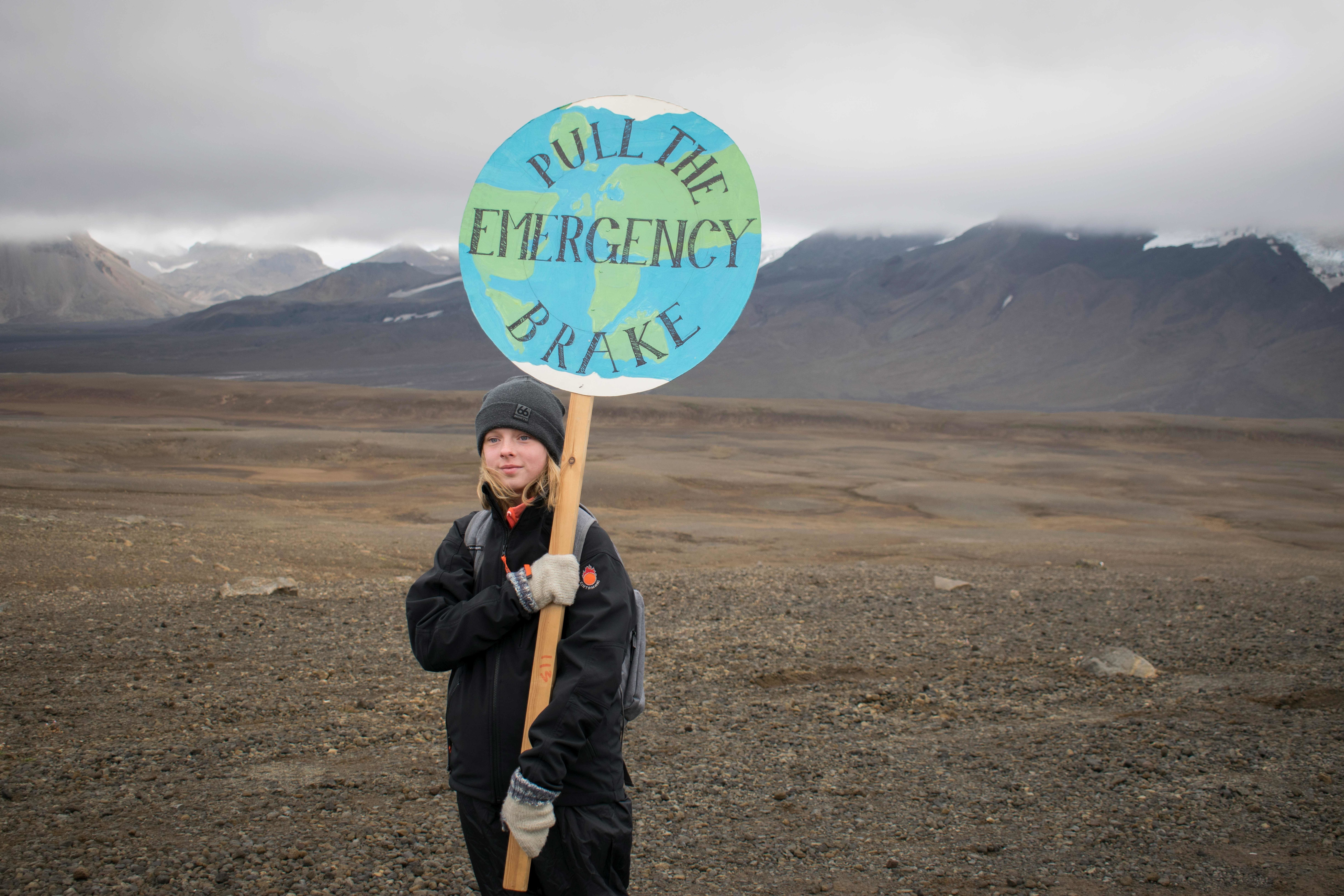 "TOPSHOT - An Icelandic girl poses for a photo with a ""Pull the emergency brake"" sign near to where a monument was unveiled at the site of Okjokull, Iceland's first glacier lost to climate change in the west of Iceland on August 18, 2019. (Photo by Jeremie RICHARD / AFP) (Photo credit should read JEREMIE RICHARD/AFP/Getty Images)"