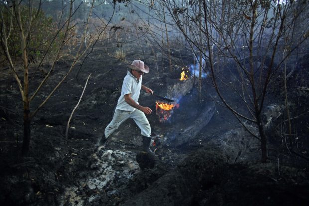 TOPSHOT - Brazilian farmer Helio Lombardo Do Santos is seen at a burnt area of the Amazon rainforest, near Porto Velho, Rondonia state, Brazil, on August 26, 2019. - Hundreds of new fires have flared up in the Amazon in Brazil, data showed Monday, even as military aircraft dumped water over hard-hit areas and G7 nations pledged to help combat the blazes. Smoke choked Port Velho city and forced the closure of the airport for nearly two hours as fires raged in the northwestern state of Rondonia where fire-fighting efforts are concentrated, amid a growing global uproar and a diplomatic spat between France and Brazil. (Photo by CARL DE SOUZA/AFP/Getty Images)