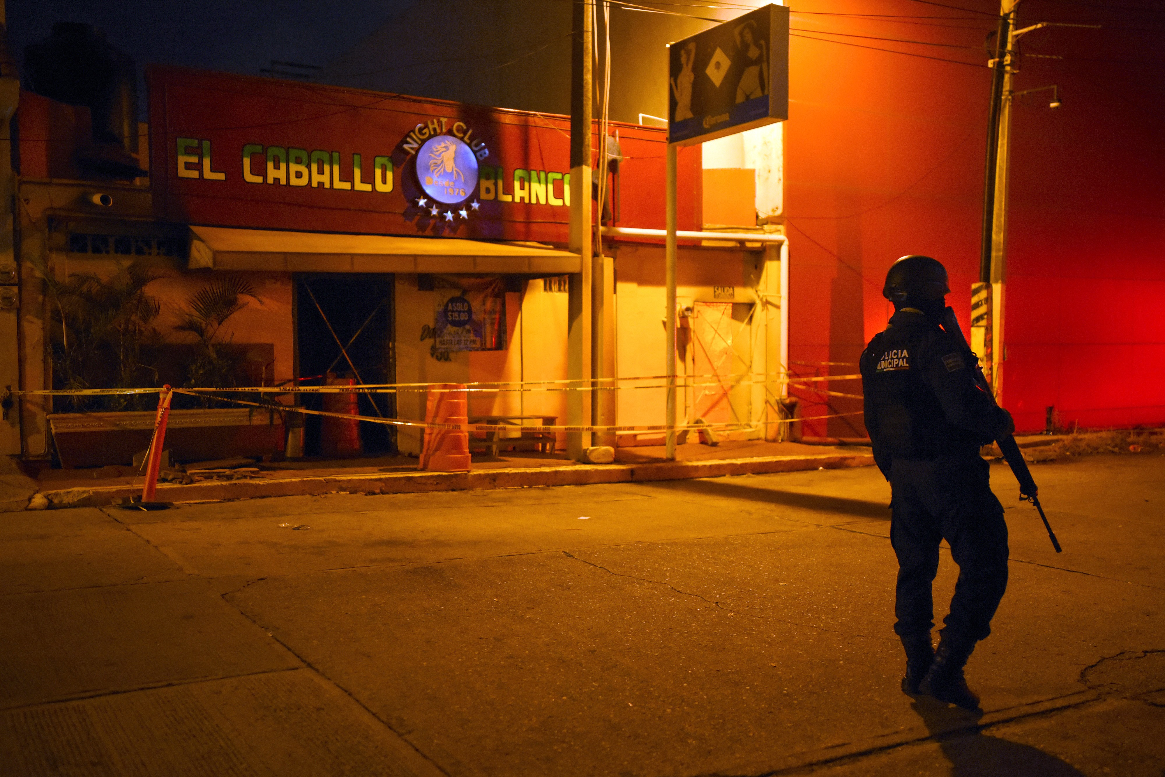 A police officer stands guard outside Caballo Blanco bar (White Horse bar) where 25 people were killed by a fire in Coatzacoalcos, Veracruz State, Mexico, on August 28, 2019. - At least 25 people were killed and 13 badly wounded in a fire which broke out Tuesday night at the bar as is being investigated as an attack, authorities said Wednesday. The state of Veracruz is a flashpoint in the bloody turf wars between Mexico's rival drug cartels. (Photo by VICTORIA RAZO / AFP) (Photo credit should read VICTORIA RAZO/AFP/Getty Images)