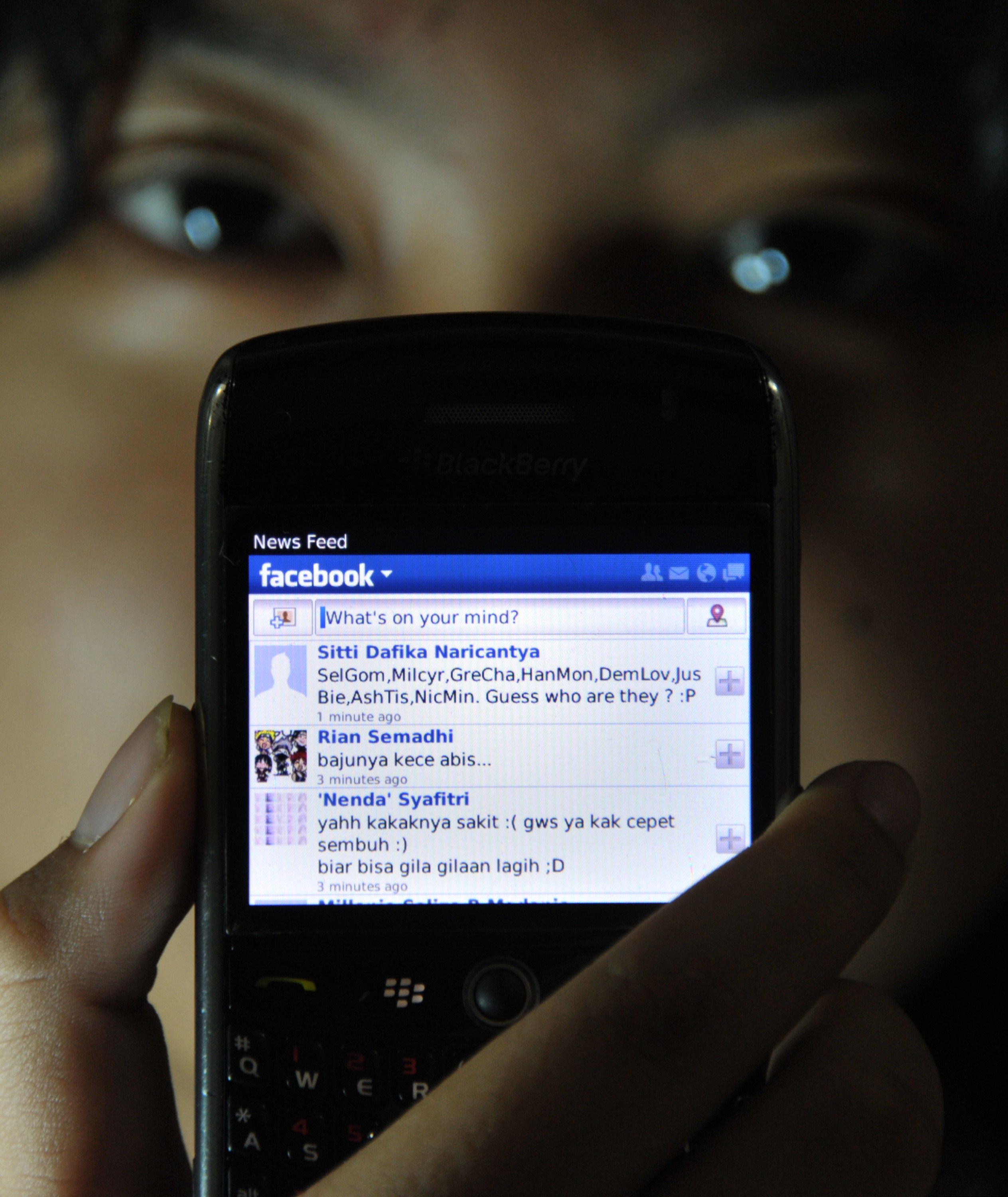 "A girl shows her Facebook ""wall"" on her mobile device. (Photo credit should read BAY ISMOYO/AFP/Getty Images)"