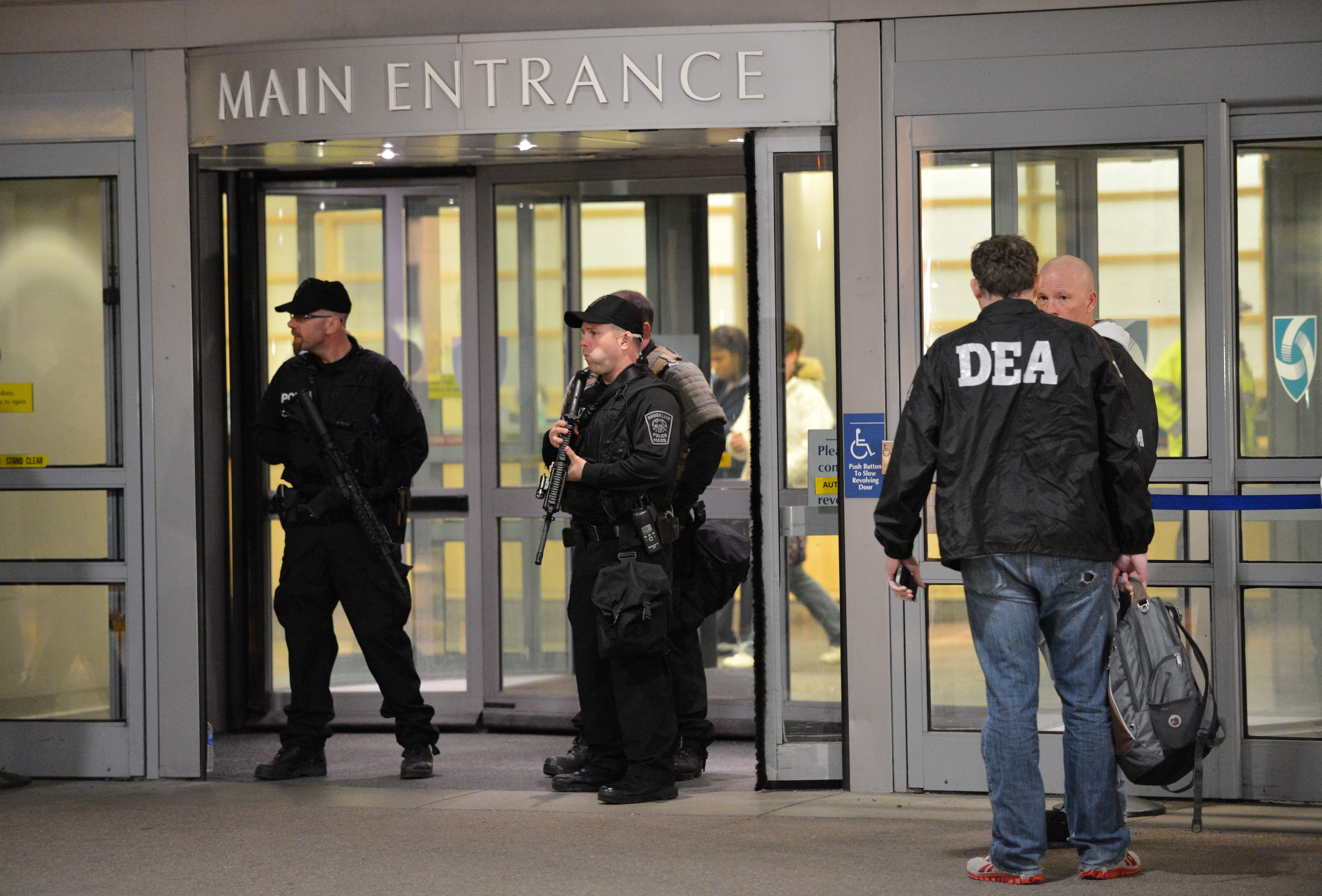 Armed police officers and Drug Enforcement Agency (DEA) agents secure the main entrance to Brigham and Women's Hospital April 15, 2013 in Boston, Massachusetts. Many who were wounded when two explosions struck near the finish line of the Boston Marathon were brought to Brigham and Women's. (STAN HONDA/AFP/Getty Images)
