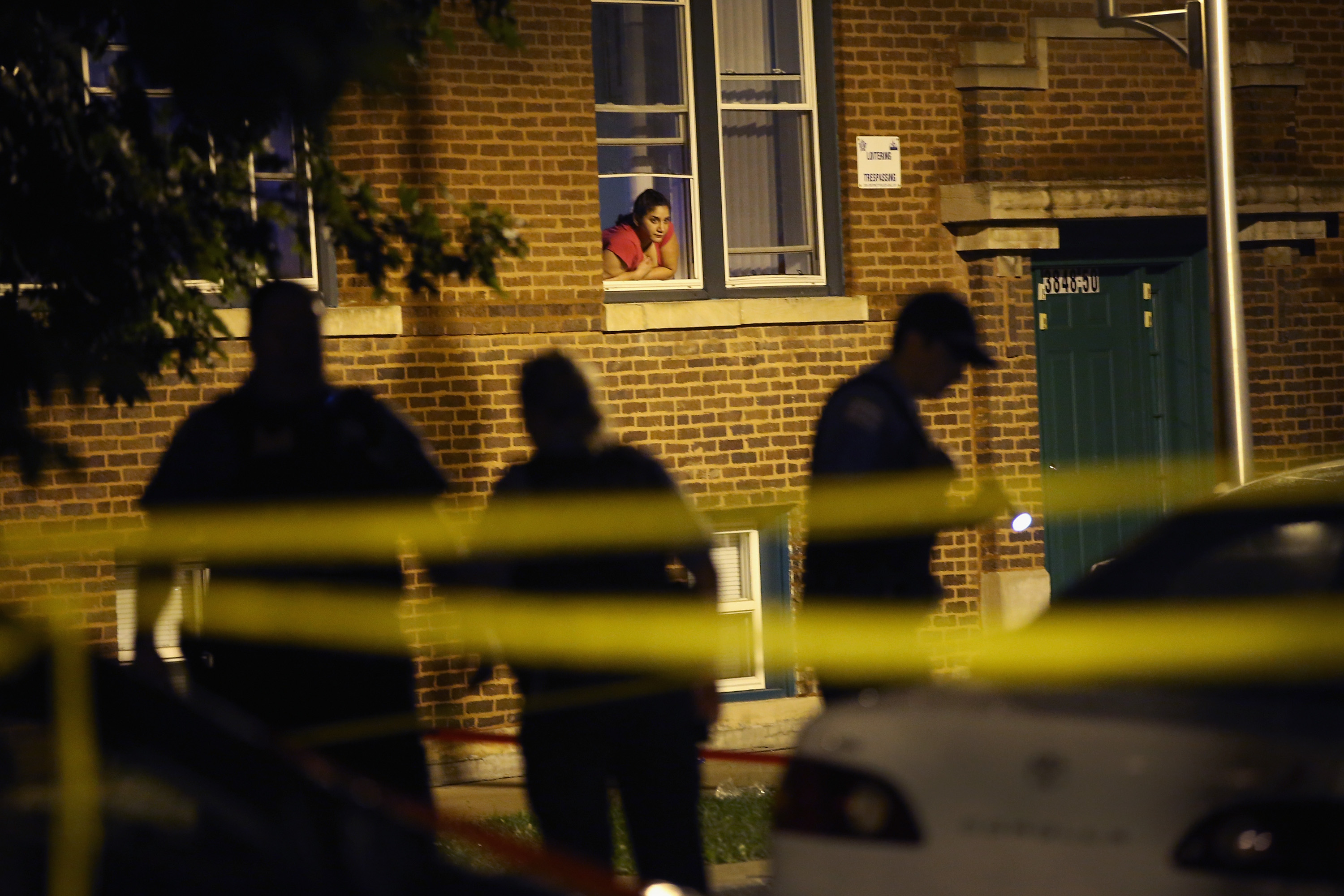 A woman watches from her window as police look for evidence after 20-year-old Carlos Barron was shot and killed in the Humboldt Park neighborhood on July 19, 2013 in Chicago, Illinois. Photo by Scott Olson/Getty Images)