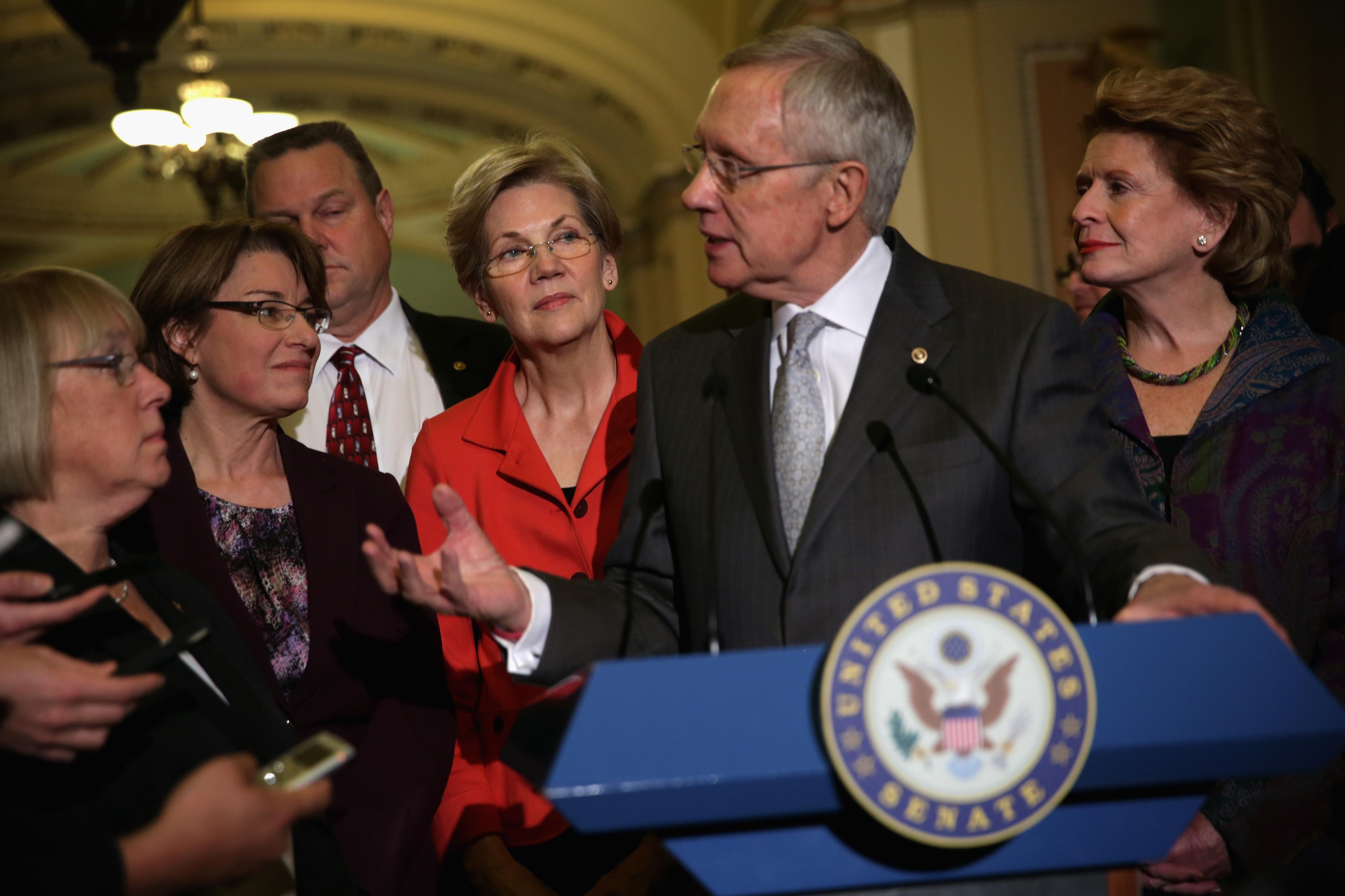 U.S. Senate Majority Leader Sen. Harry Reid (D-NV) (5th L) speaks to members of the media as (L-R) Sen. Patty Murray (D-WA), Sen. Amy Klobuchar (D-MN), Sen. Jon Tester (D-MT), Sen. Elizabeth Warren (D-MA), and Sen. Debbie Stabenow (D-MI) listen. (Alex Wong/Getty Images)
