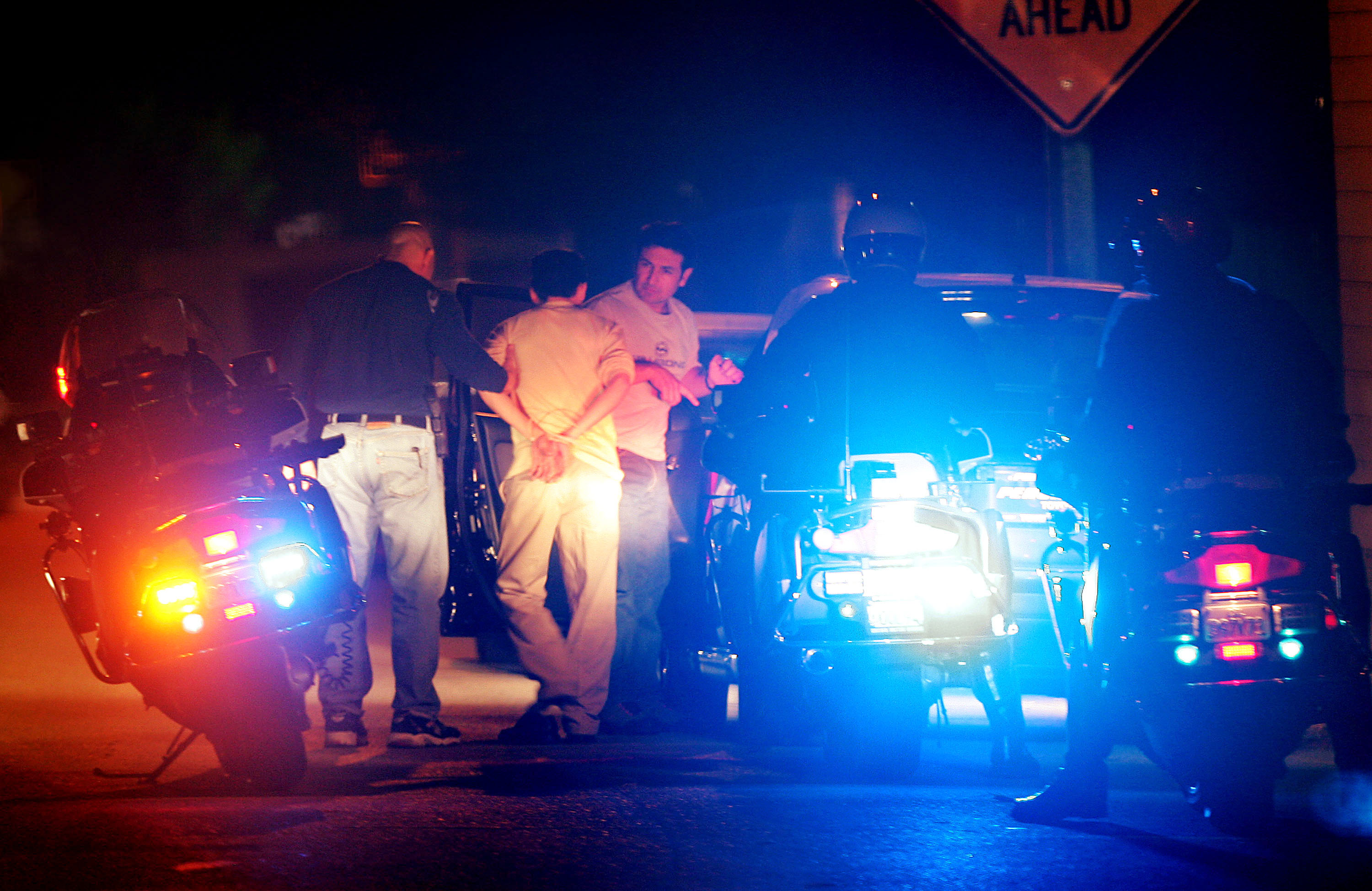 """POMONA, CA - NOVEMBER 12: A man is arrested by police after he stopped his car to talk to a female police officer posing as a prostitute on Holt Boulevard, known to sex workers throughout southern California as """"the track"""", during a major prostitution sting operation November 12, 2004 in Pomona, California. Approximately 60 to 80 men are arrested each night during the sting operations. Cars driven by the arrested men are seized and become city property until a $1000 fine is paid. Each vehicle is then labeled with a large window sticker stating that the car was ?seized for solicitation of prostitution? and the photos of the men appear in a full-page ad in the local newspaper. (Photo by David McNew/Getty Images)"""