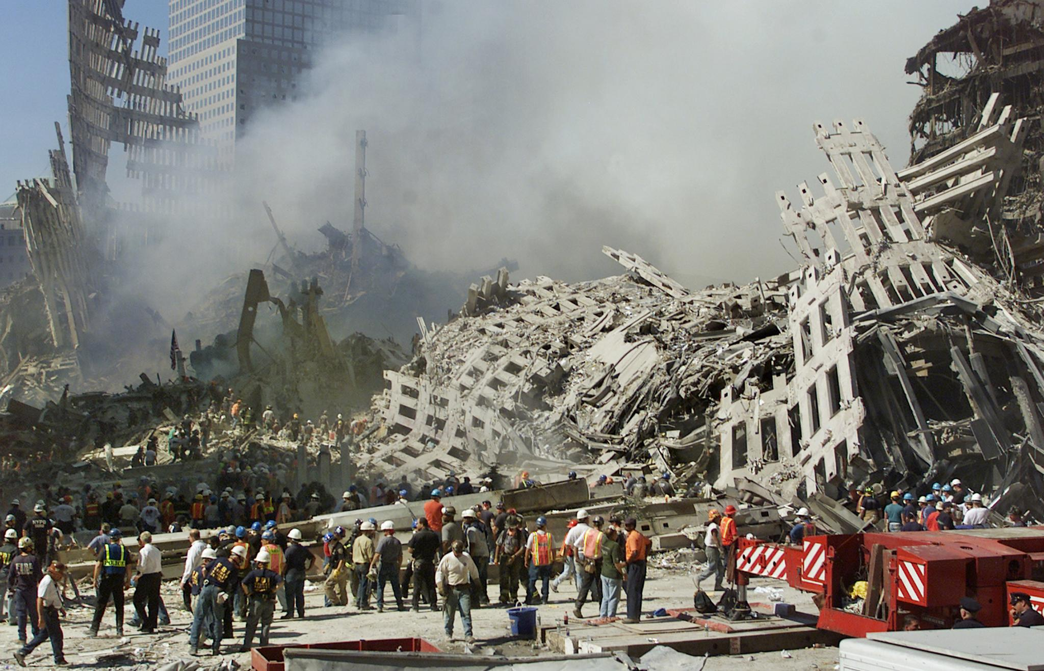 Rescue workers continue their search as smoke rises from the rubble of the World Trade Center 13 September 2001 in New York. (BETH A. KEISER/AFP/Getty Images)