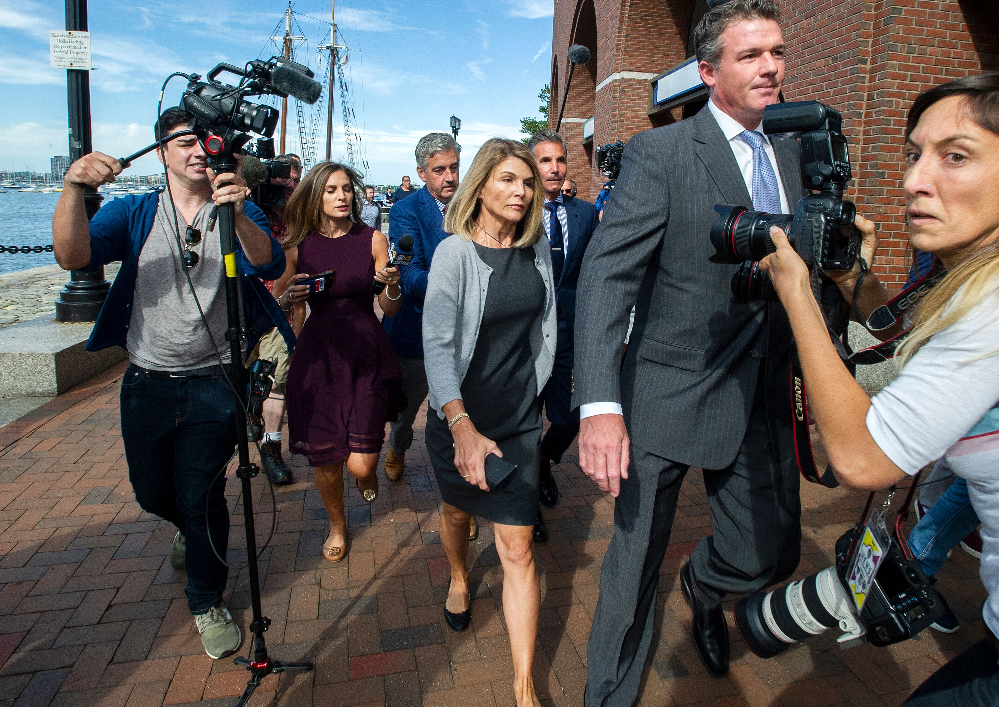 Actress Lori Loughlin (C) and husband Mossimo Giannulli (C rear) exit the Boston Federal Court house after a pre-trial hearing with Magistrate Judge Kelley at the John Joseph Moakley US Courthouse in Boston on August 27, 2019. - Loughlin and Giannulli are charged with conspiracy to commit mail and wire fraud and conspiracy to commit money laundering in the college admissions scandal. (Photo credit JOSEPH PREZIOSO/AFP/Getty Images)