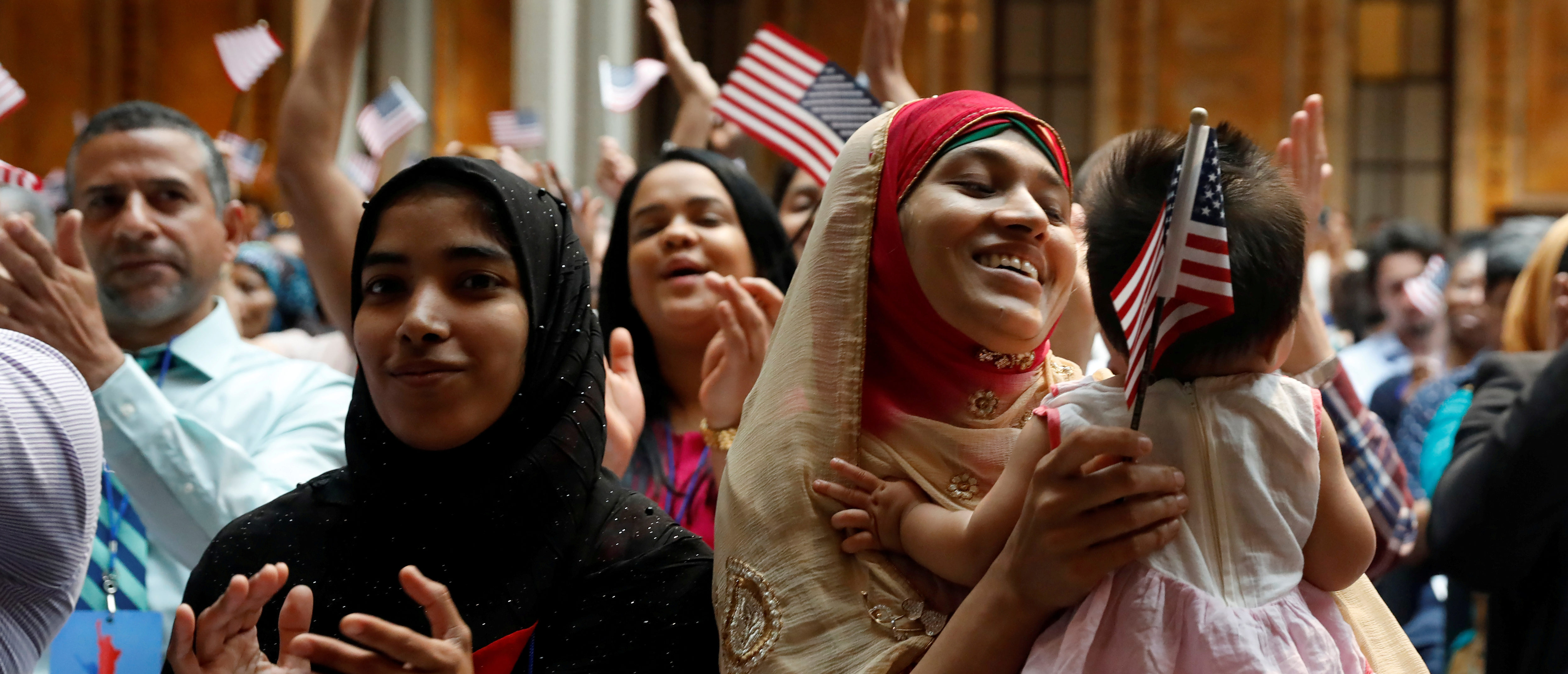 New citizens smile at a U.S. Citizenship and Immigration Services (USCIS) naturalization ceremony at the New York Public Library in Manhattan