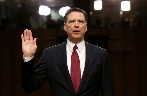 FILE PHOTO: Former FBI Director James Comey is sworn in prior to testifying before a Senate Intelligence Committee hearing on Russia's alleged interference in the 2016 U.S. presidential election on Capitol Hill in Washington, U.S., June 8, 2017. REUTERS/Jonathan Ernst/Files
