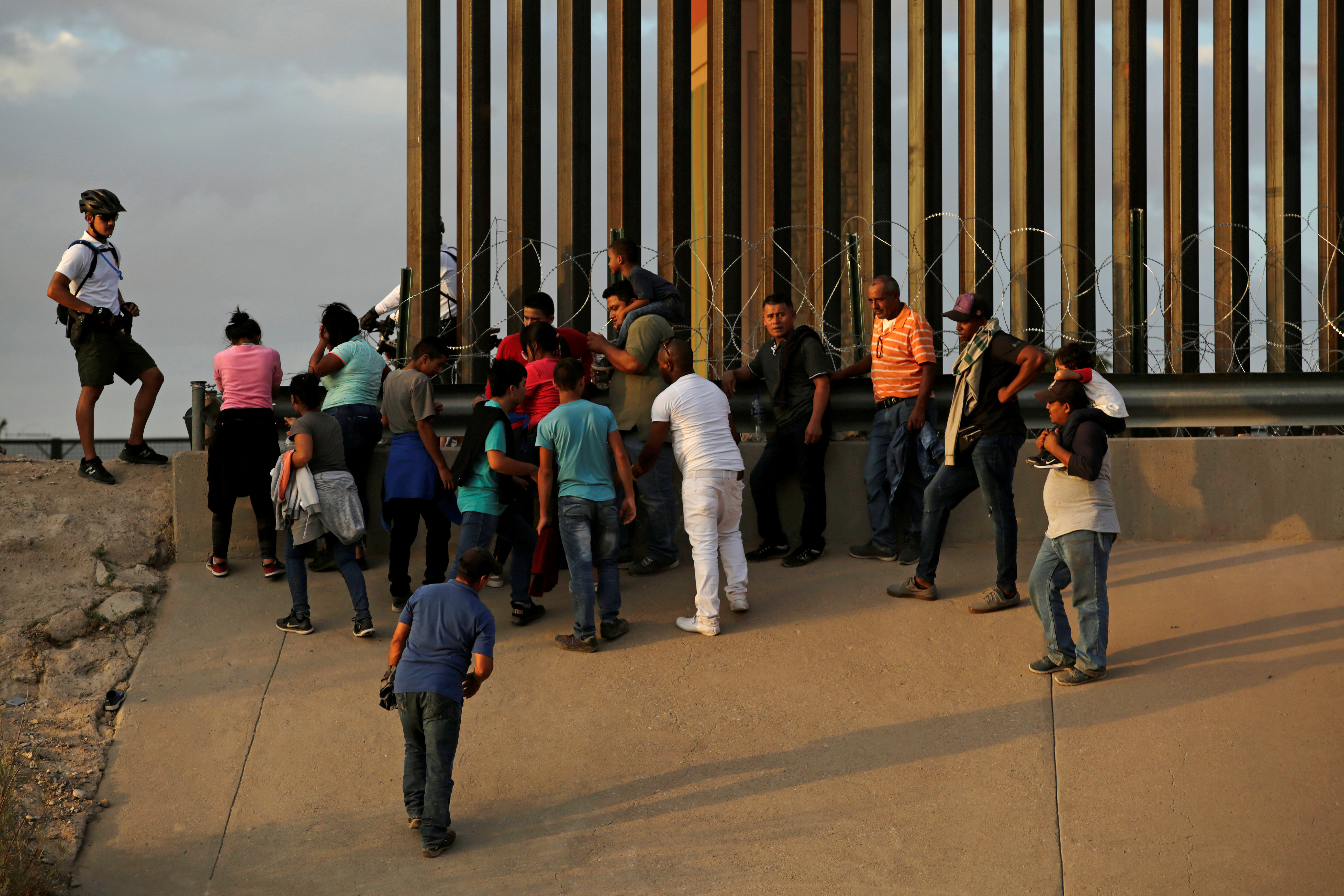 A U.S. Customs and Border Protection (CBP) agent stands next to migrants who crossed illegally into El Paso, Texas, U.S. to turn themselves in to ask for asylum, as seen from Ciudad Juarez, Mexico July 31, 2019. REUTERS/Jose Luis Gonzalez