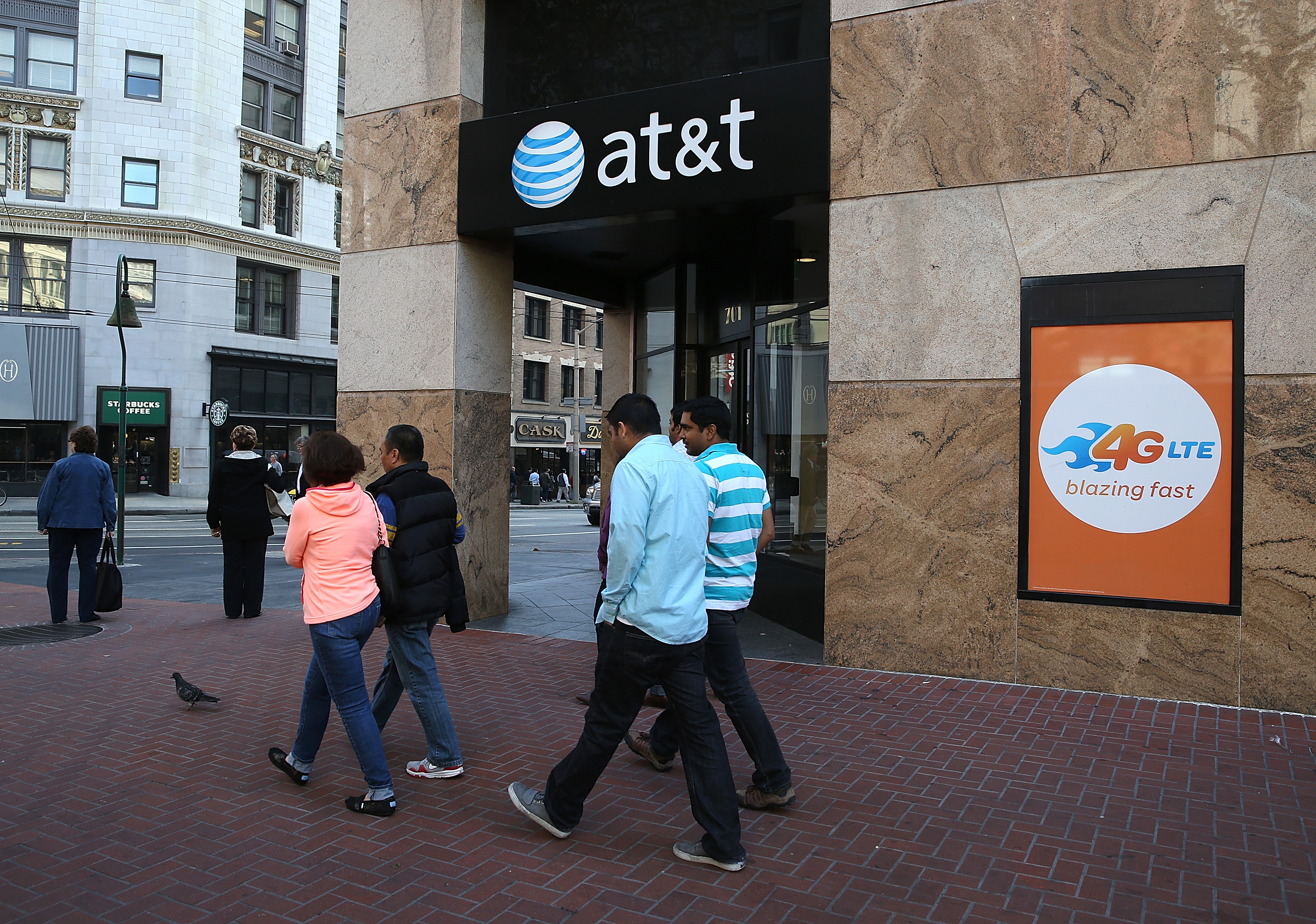 SAN FRANCISCO, CA - OCTOBER 23: Pedestrians walk by an AT&T store on October 23, 2013 in San Francisco, California. AT&T is going to report third quarter earnings after the closing bell. (Photo by Justin Sullivan/Getty Images)