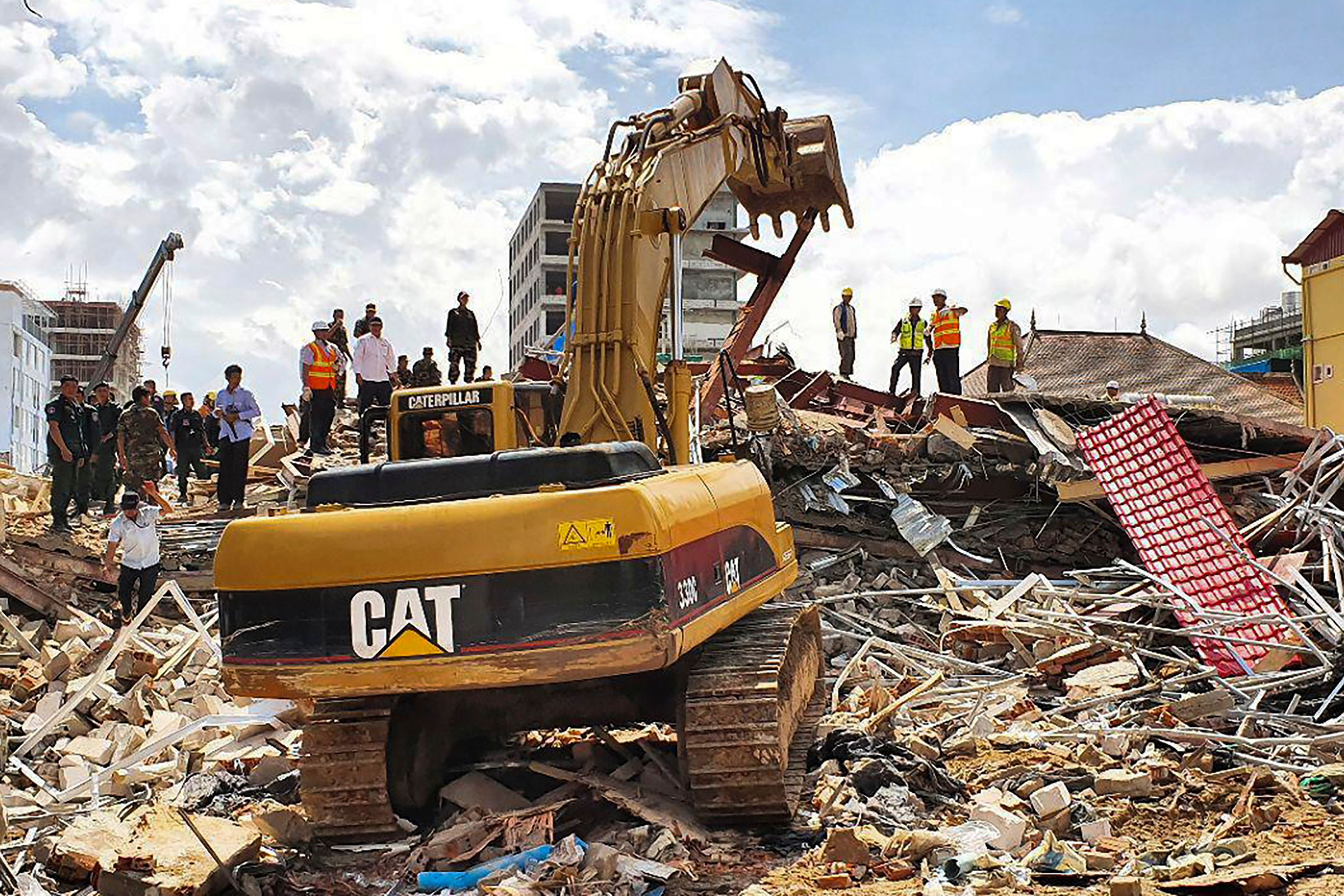 Rescue workers use an earthmover to clear debris after an under-construction building collapsed in Sihanoukville June 22, 2109. - At least three people died when an under-construction building collapsed in a Cambodian beach resort early on June 22, officials said, with fears dozens more may be buried in the rubble. (Photo by LY LAY/AFP/Getty Images)