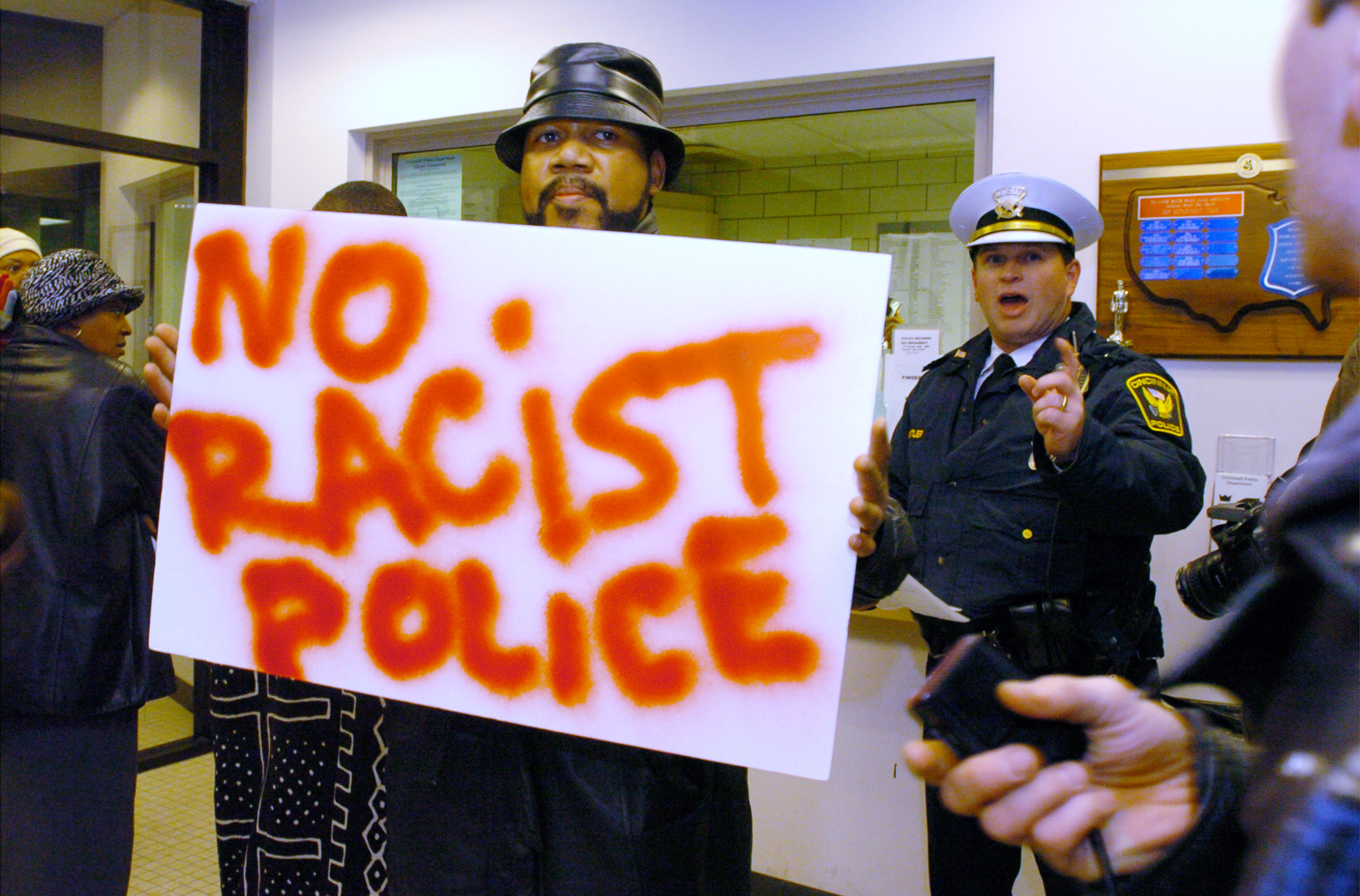 "CINCINNATI, OH - DECEMBER 5: A Cincinnati Police officer asks protesters to leave after they entered Cincinnati Police Headquarters to deliver ""eviction notices"" for Chief Tom Streicher December 5, 2003 in Cincinnati, Ohio. A group of about 30 protesters showed up to protest the death of Nathaniel Jones, who died while being arrested by Cincinnati Police. (Photo by Mike Simons/Getty Images)"