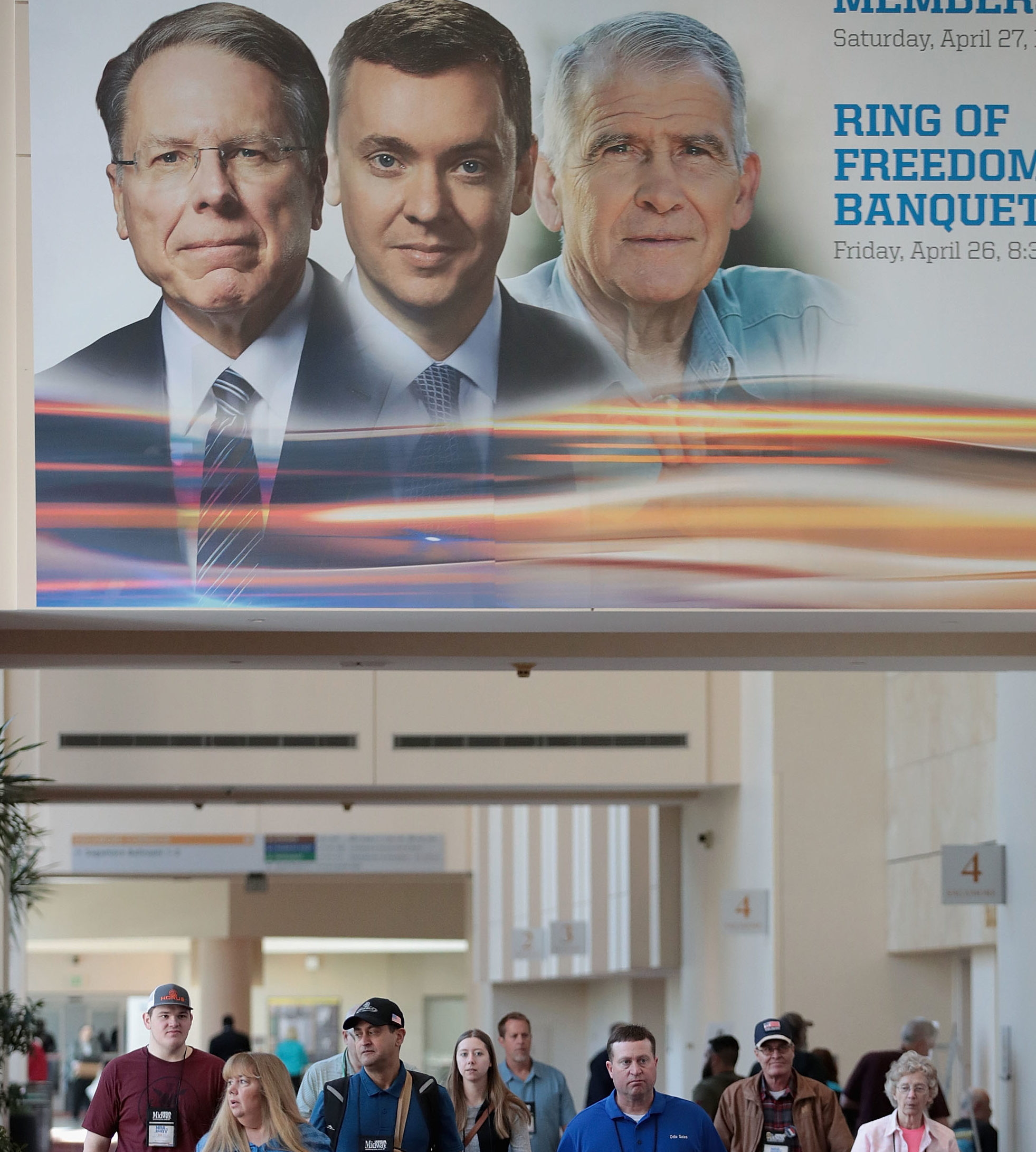 Guest walk under a poster featuring Wayne LaPierre (L), NRA vice president and CEO, Chris Cox (C), executive director of the NRA-ILA, and NRA president Oliver North outside a conference room where the NRA annual meeting of members was being held at the 148th NRA Annual Meetings and Exhibits on April 27, 2019 in Indianapolis, Indiana. After much-publicized group infighting, only La Pierre remains. (Photo by Scott Olson/Getty Images)