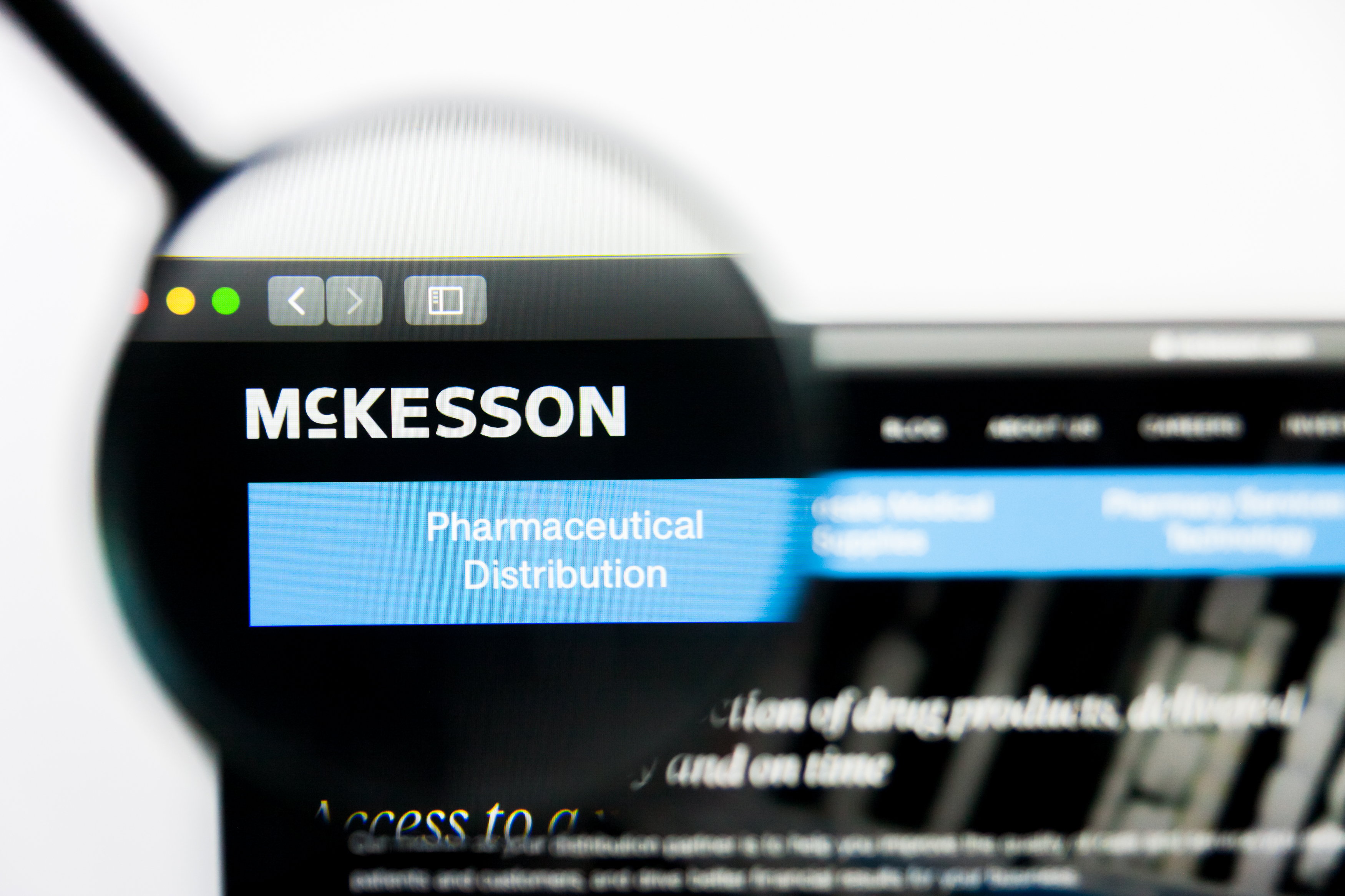 A magnifying glass zooms in on the website for McKesson. Shutterstock image via Pavel Kapysh