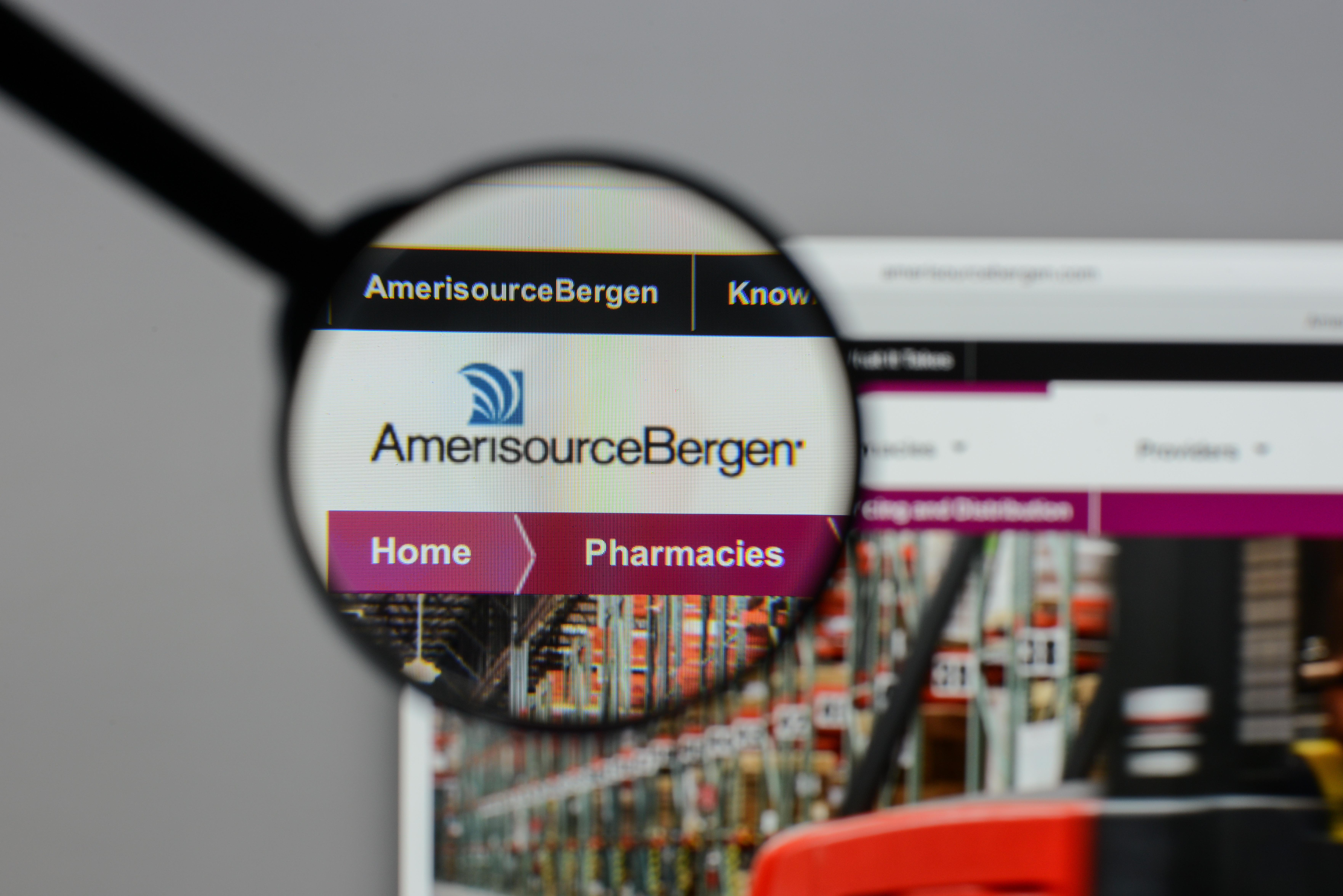 A magnifying glass zooms in on the website for AmerisourceBergen. Shutterstock image via Casimiro PT