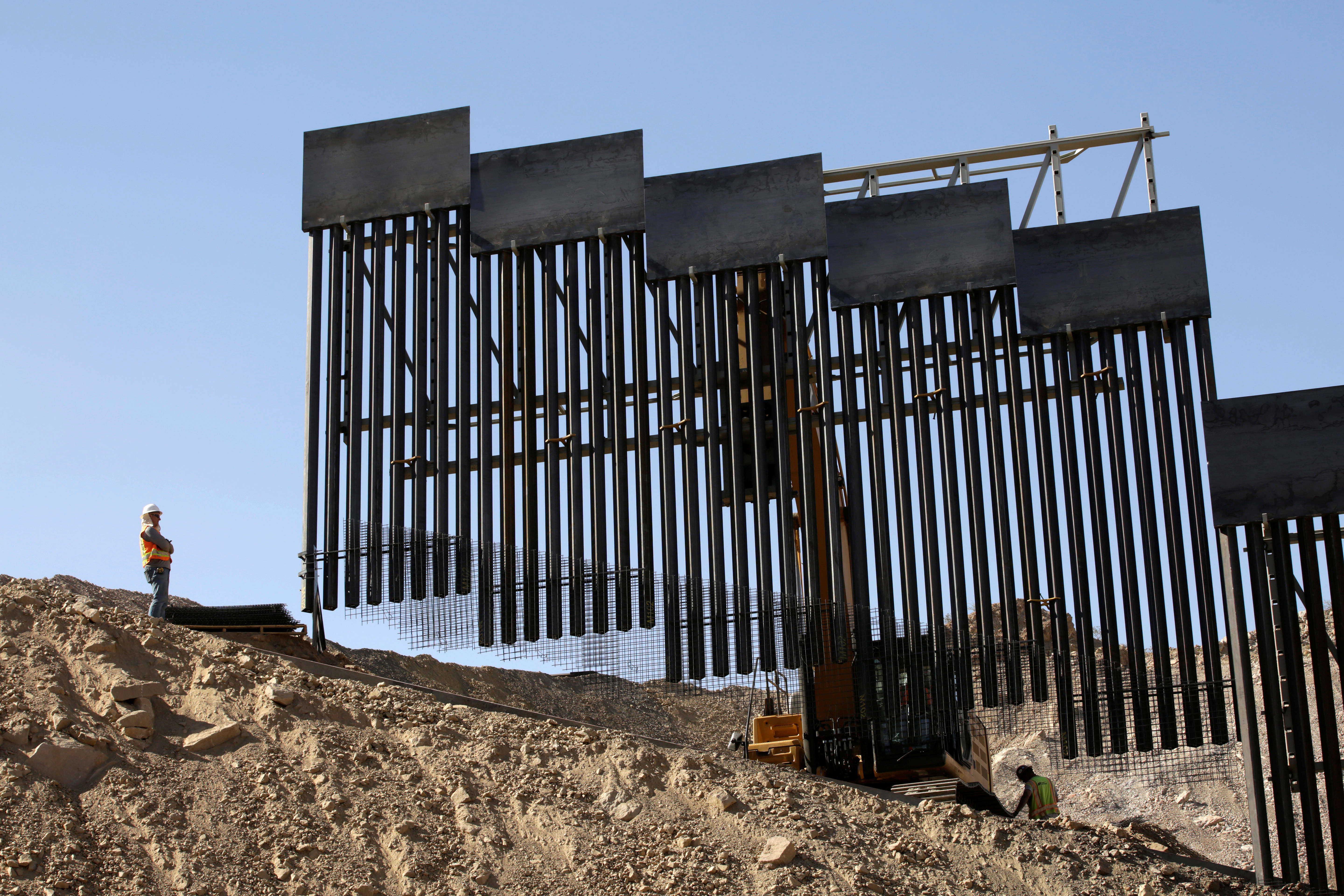 A construction crew works on a bollard-type private border wall, crowd-funded by We Build The Wall group at Sunland Park, New Mexico, as pictured from Ciudad Juarez