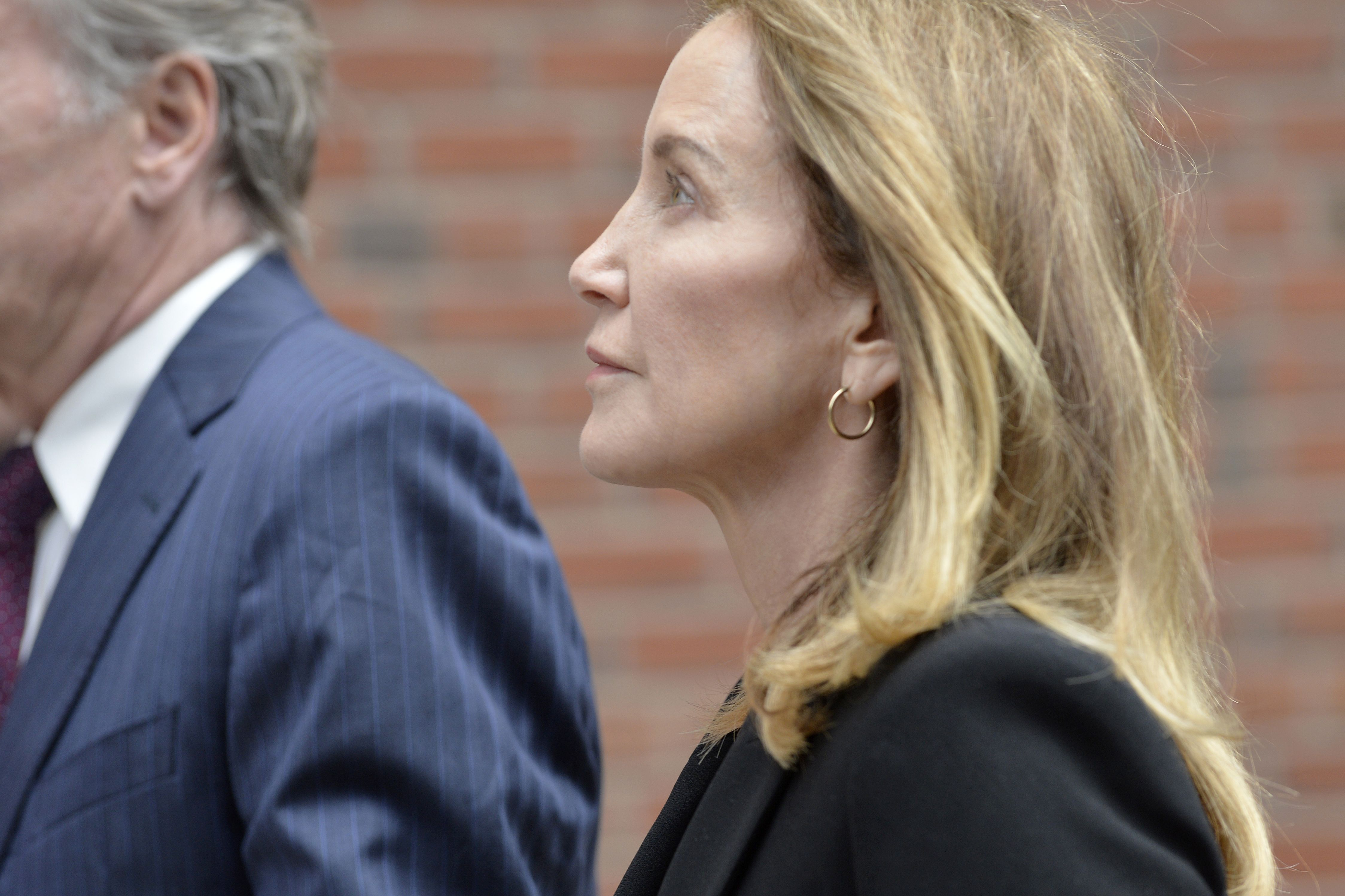 Actress Felicity Huffman is escorted by police into court where she is expected to plead guilty to one count of conspiracy to commit mail fraud and honest services mail fraud before Judge Talwani at John Joseph Moakley United States Courthouse in Boston, Massachusetts, May 13, 2019. (Photo credit JOSEPH PREZIOSO/AFP/Getty Images)