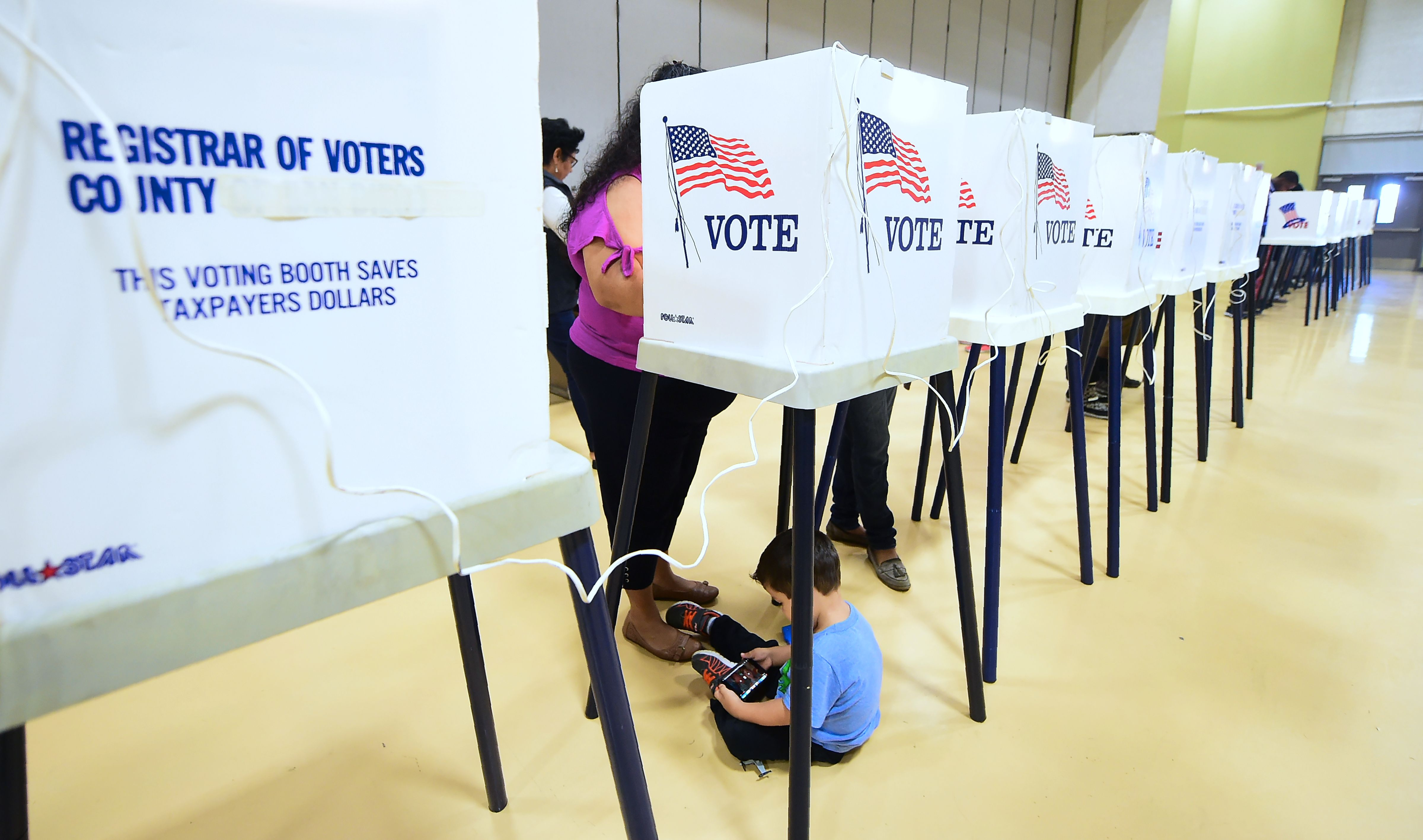A woman votes from a booth as her child plays with a cellphone below inside the gymnasium at the Barack Obama Prep Academy on November 6, 2018 in Los Angeles, California. - Americans started voting Tuesday in critical midterm elections that mark the first major voter test of Donald Trump's controversial presidency, with control of Congress at stake. About three quarters of the 50 states in the east and center of the country were already voting as polls began opening at 6:00 am (1100 GMT) for the day-long ballot.