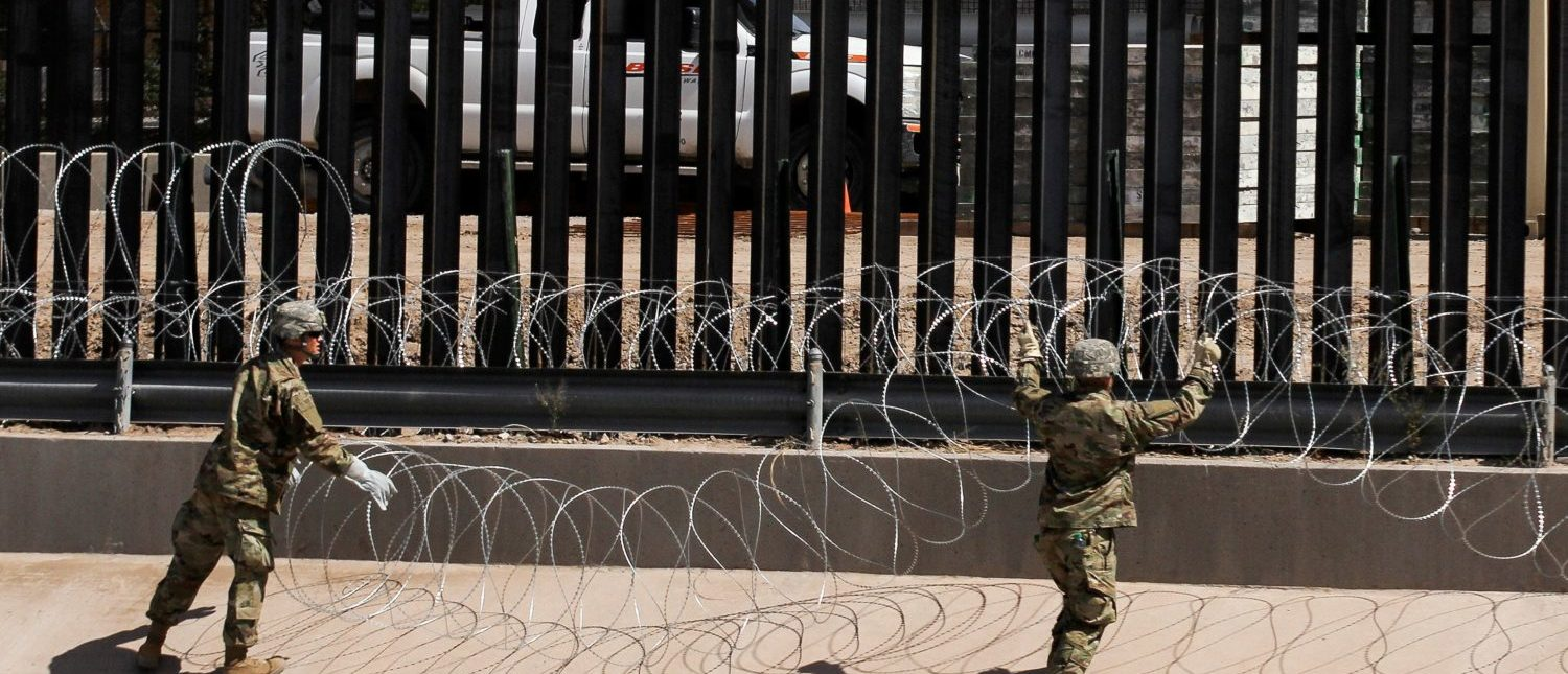 U.S. soldiers install barb wire by the US-Mexico border fence in El Paso, Texas state, US, as seen from Ciudad Juarez, Chihuahua state, Mexico on April 4, 2019. - US President Donald Trump is expected to visit a section of the border fence in Calexico during his tour to California on Friday. (Photo by HERIKA MARTINEZ/AFP/Getty Images)