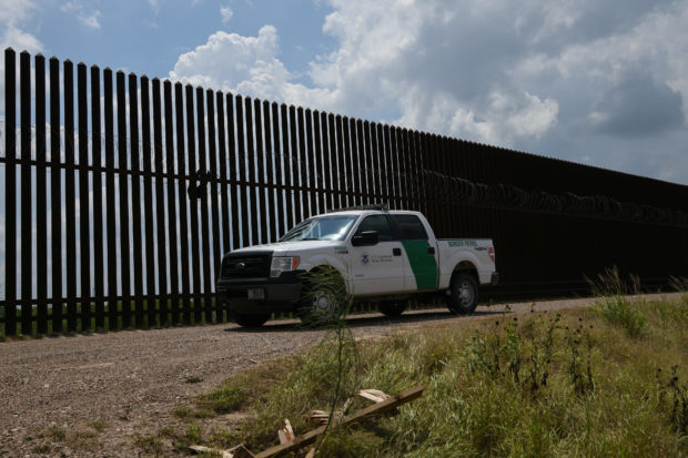 A US Border Patrol vehicle drives along a section of border fence near the US-Mexico border on June 12, 2019, in Hidalgo, Texas. (Photo by Loren ELLIOTT / AFP) (Photo credit should read LOREN ELLIOTT/AFP/Getty Images)
