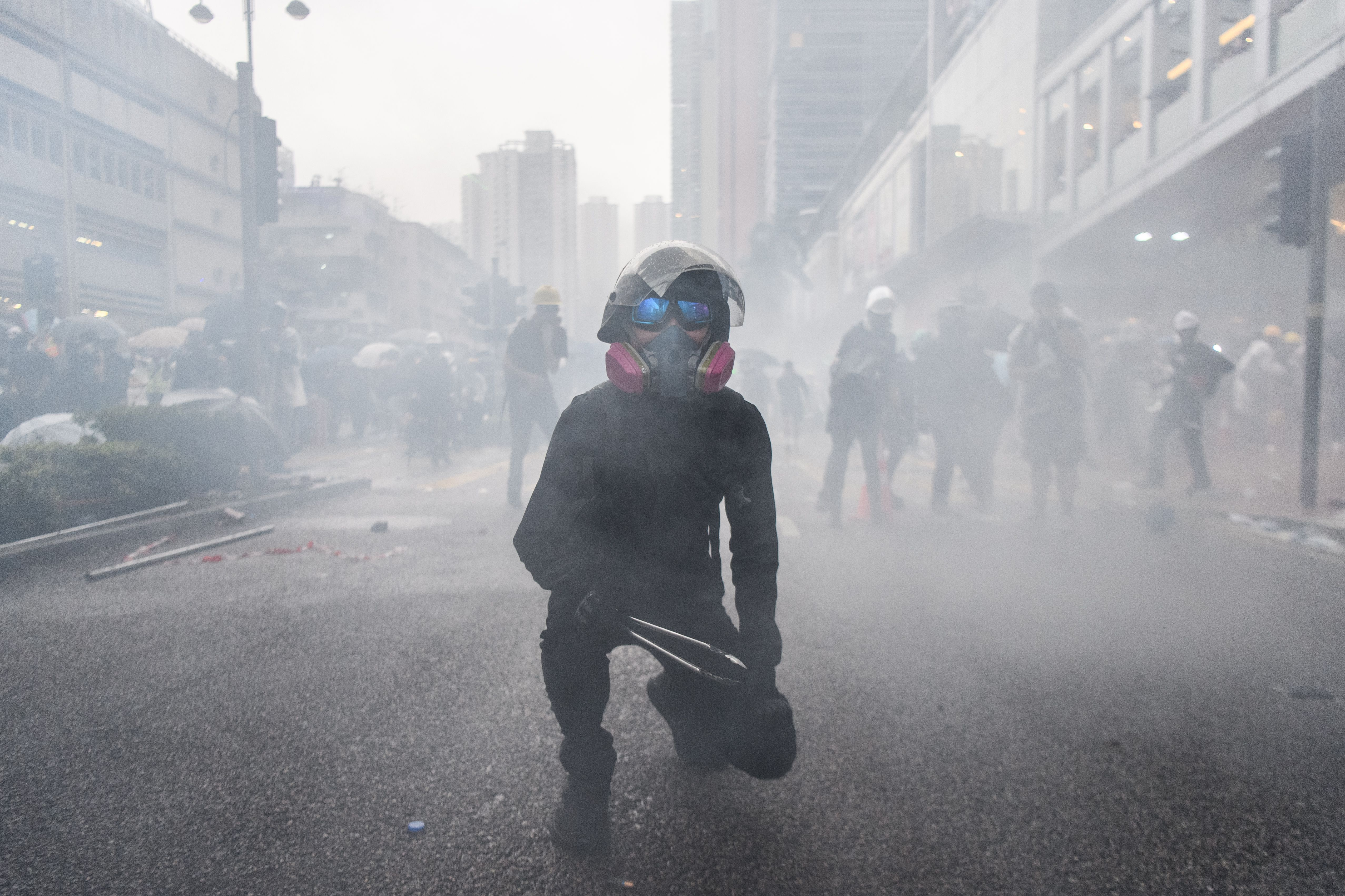 Nick, 20, (C) holds metal cooking tongs as he waits for police to fire more tear gas rounds, shortly after he became seperated from his girlfriend Abby, 19, during a protest in Tsuen Wan, an area in the New Territories in Hong Kong. - (ANTHONY WALLACE/AFP/Getty Images)
