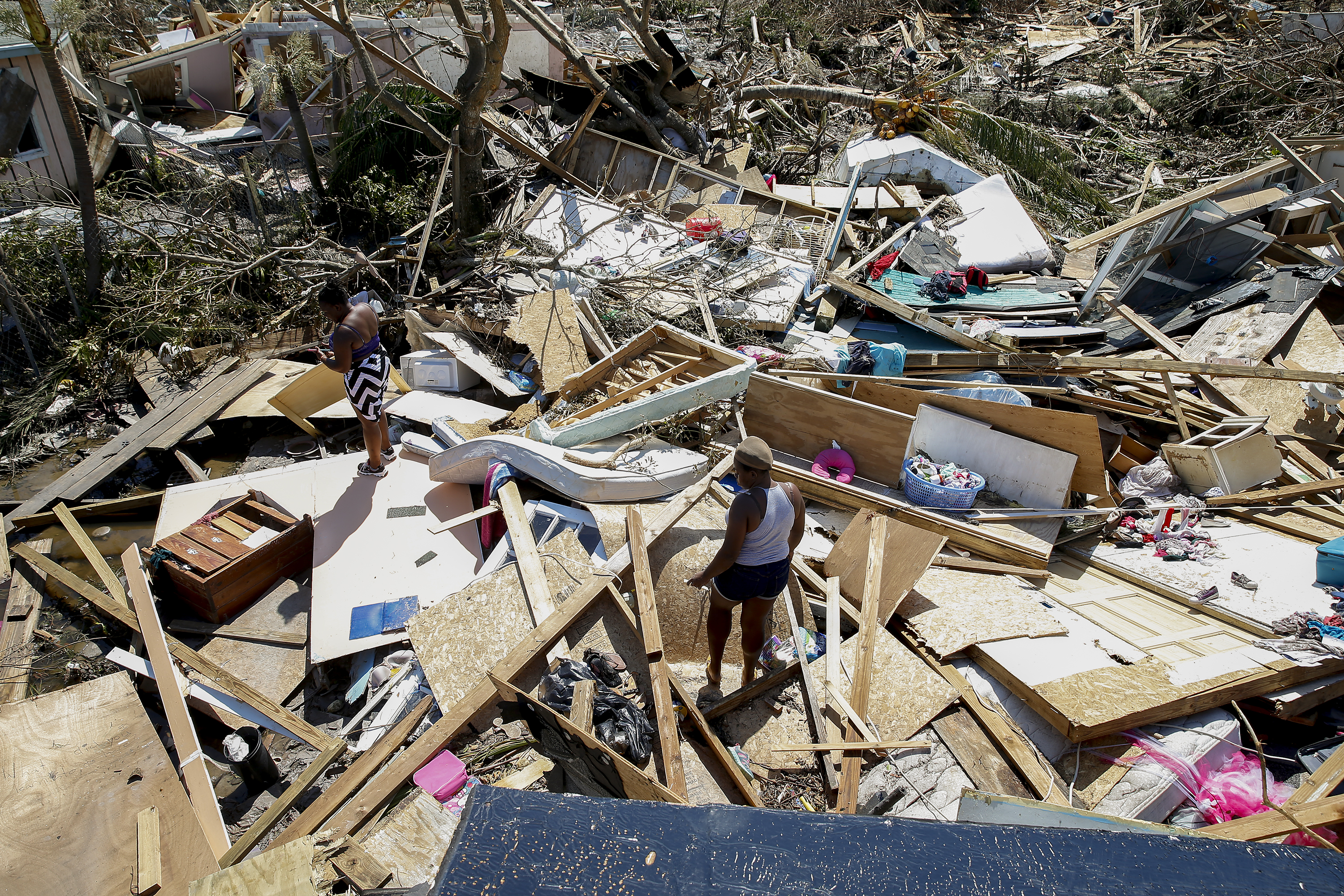 Two women look for lost items after Hurricane Dorian passed through in The Mudd area of Marsh Harbour on September 5, 2019 in Great Abaco Island, Bahamas. (Jose Jimenez/Getty Images)
