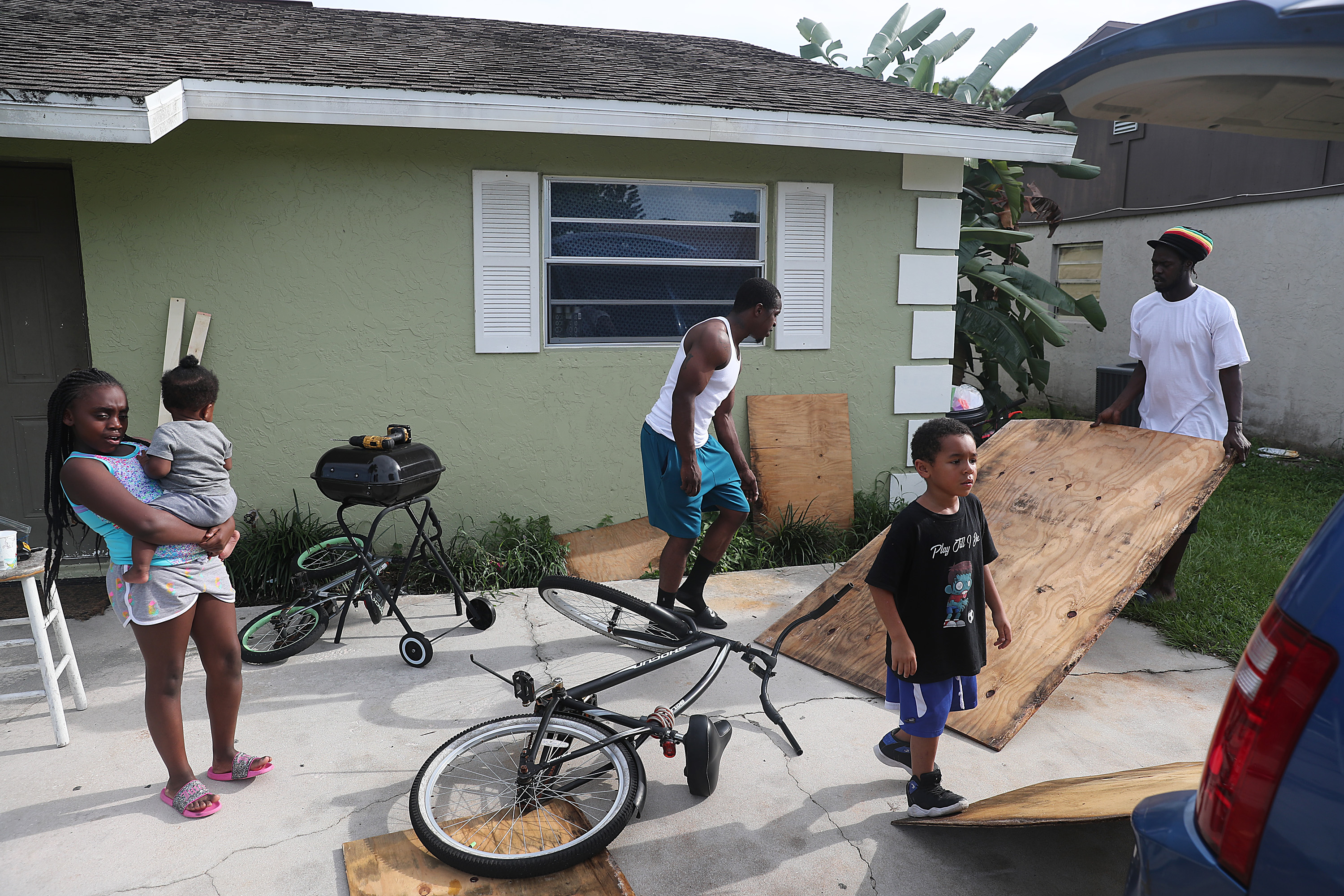 Langdon Bryant (R) and Marcus McClain (C) prepare to hang plywood over a window as they protect their home just in case Hurricane Dorian hits the area on September 01, 2019 in Port Salerno, Florida. (Joe Raedle/Getty Images)