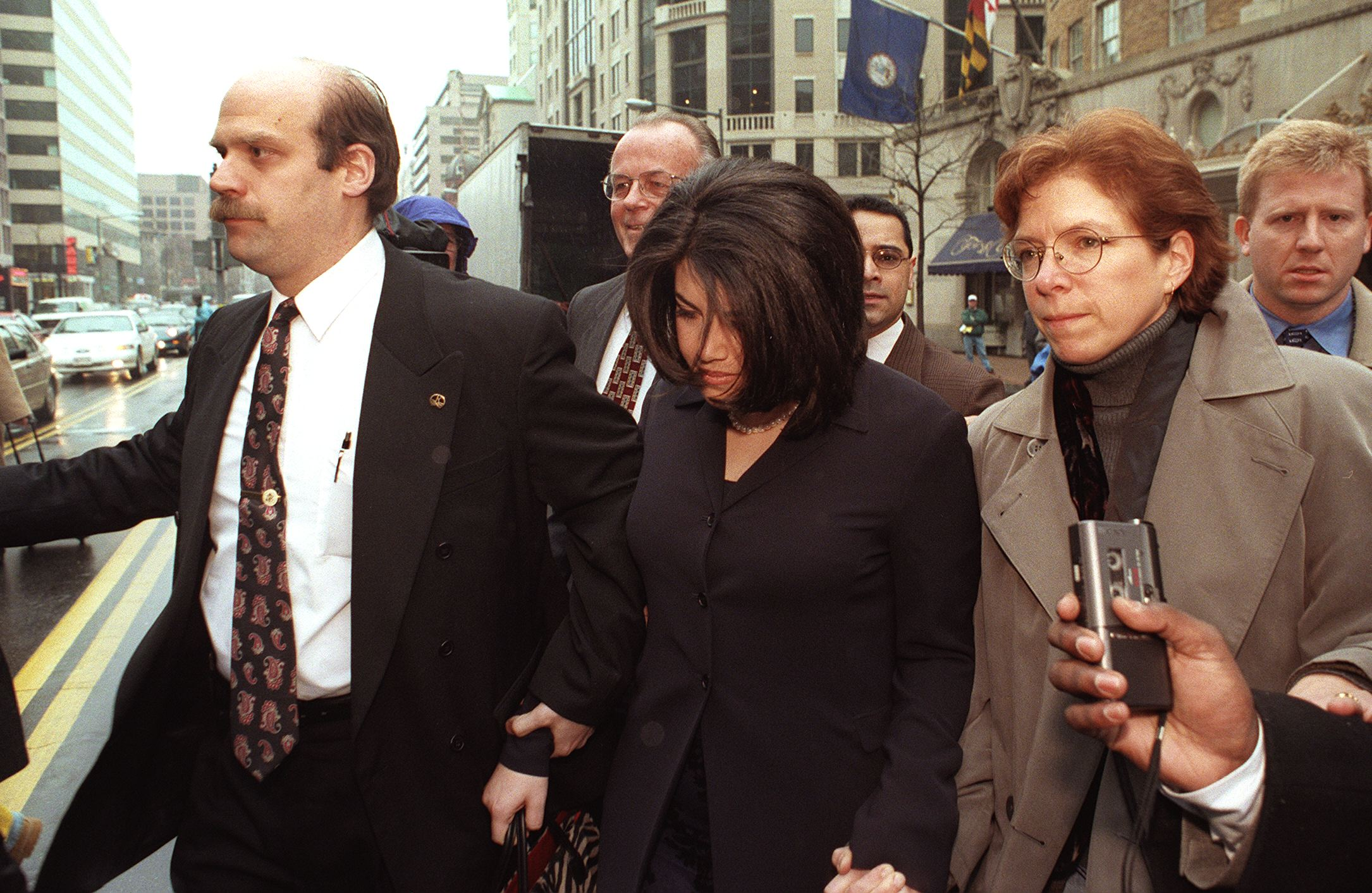 WASHINGTON, : Former White House intern Monica Lewinsky(C) is escorted across Connecticut Avenue 02 February in Washington, DC, enroute to her attorneys office. Lewinsky gave a deposition 01 February as a witness in the impeachment trial of US President Bill Clinton currently in progress in the senate. AFP PHOTO/Chris KLEPONIS (Photo credit should read CHRIS KLEPONIS/AFP/Getty Images)