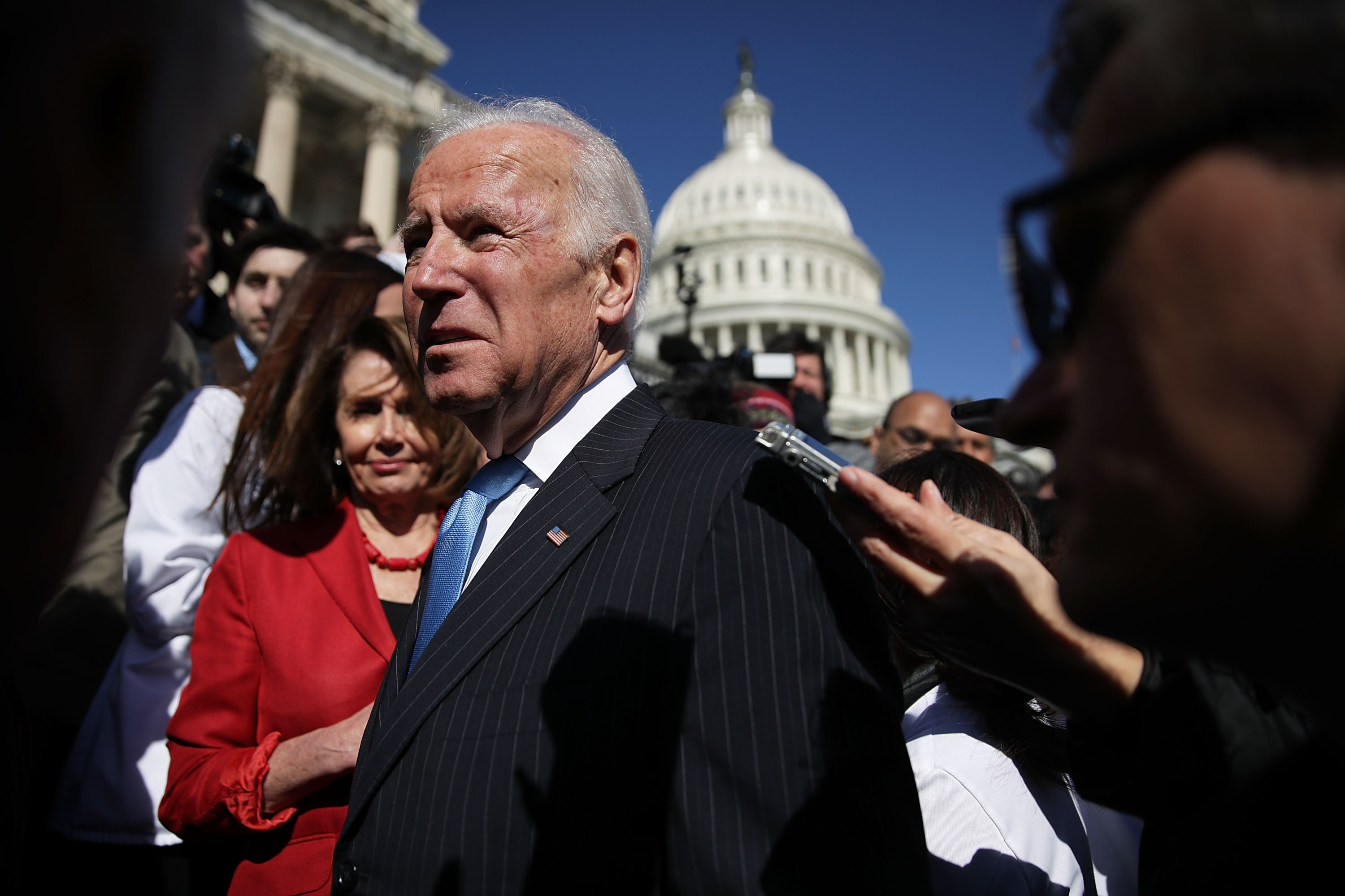 WASHINGTON, DC - MARCH 22: Former U.S. Vice President Joseph Biden speaks to members of the media as House Minority Leader Rep. Nancy Pelosi (D-CA) looks on after an event on health care at the House East Front of the Capitol March 22, 2017 in Washington, DC. House Democrats held the event to mark the seventh anniversary of the Affordable Care Act. (Photo by Alex Wong/Getty Images)